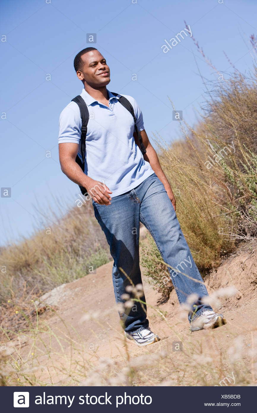 Man walking a trail in the countryside. - Stock Image