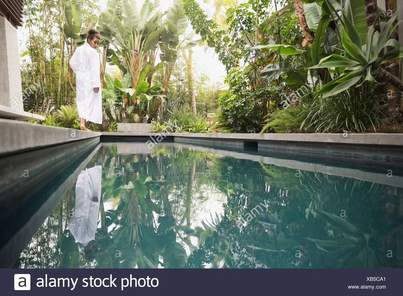Woman walking at the edge of swimming pool Stock Photo