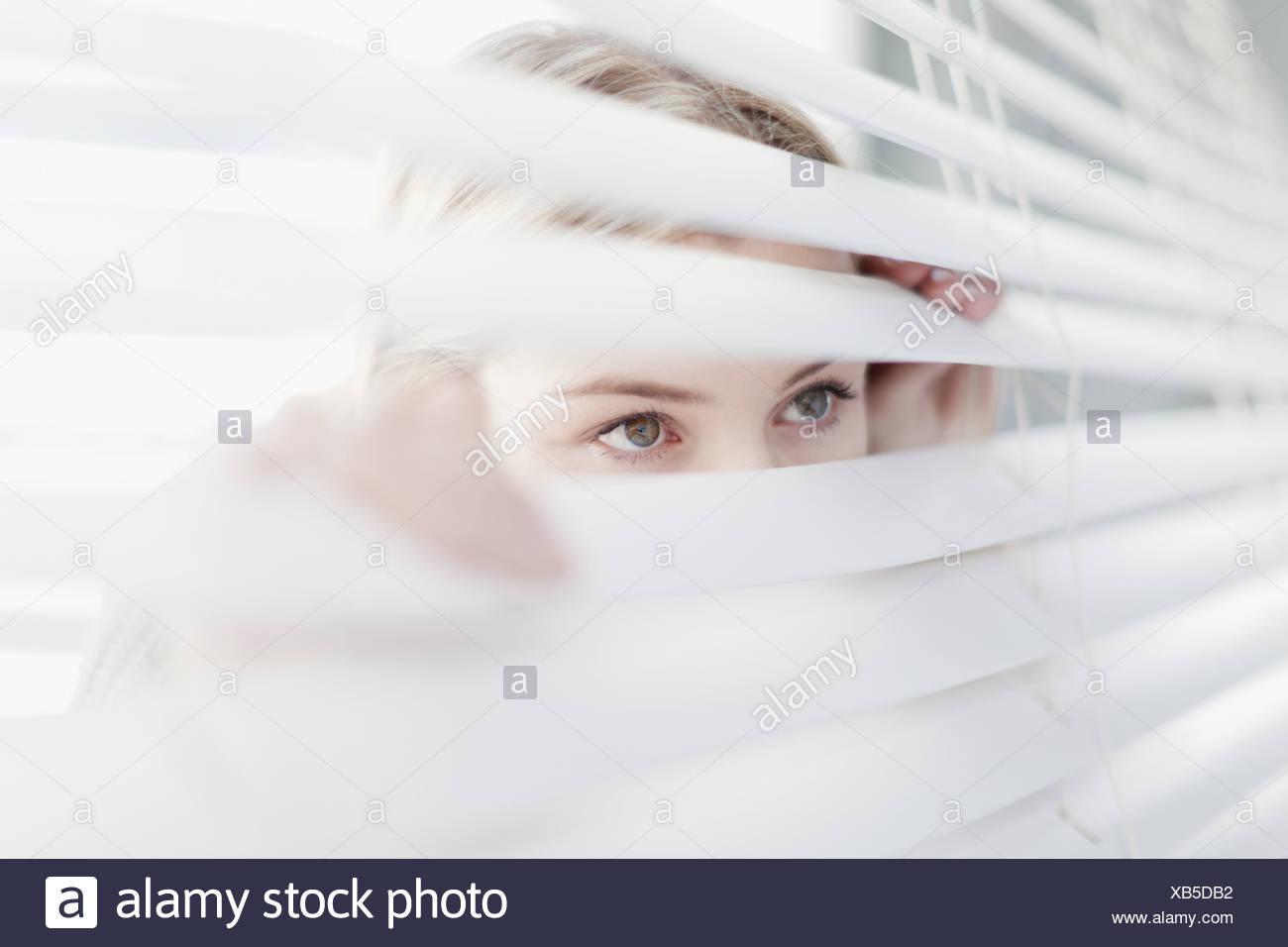Teenage girl peering through blinds - Stock Image
