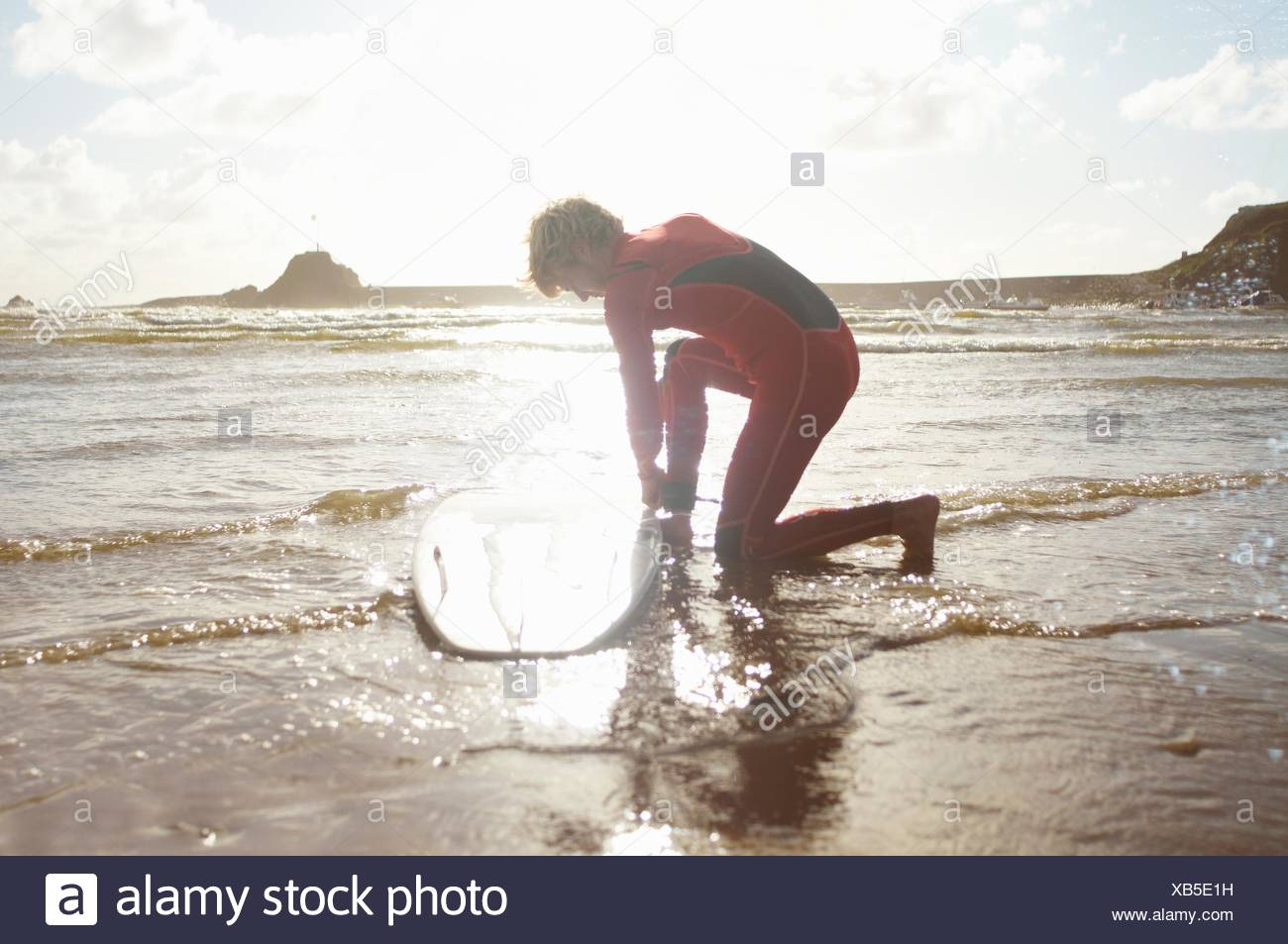 Male surfer untying surfboard from ankle - Stock Image