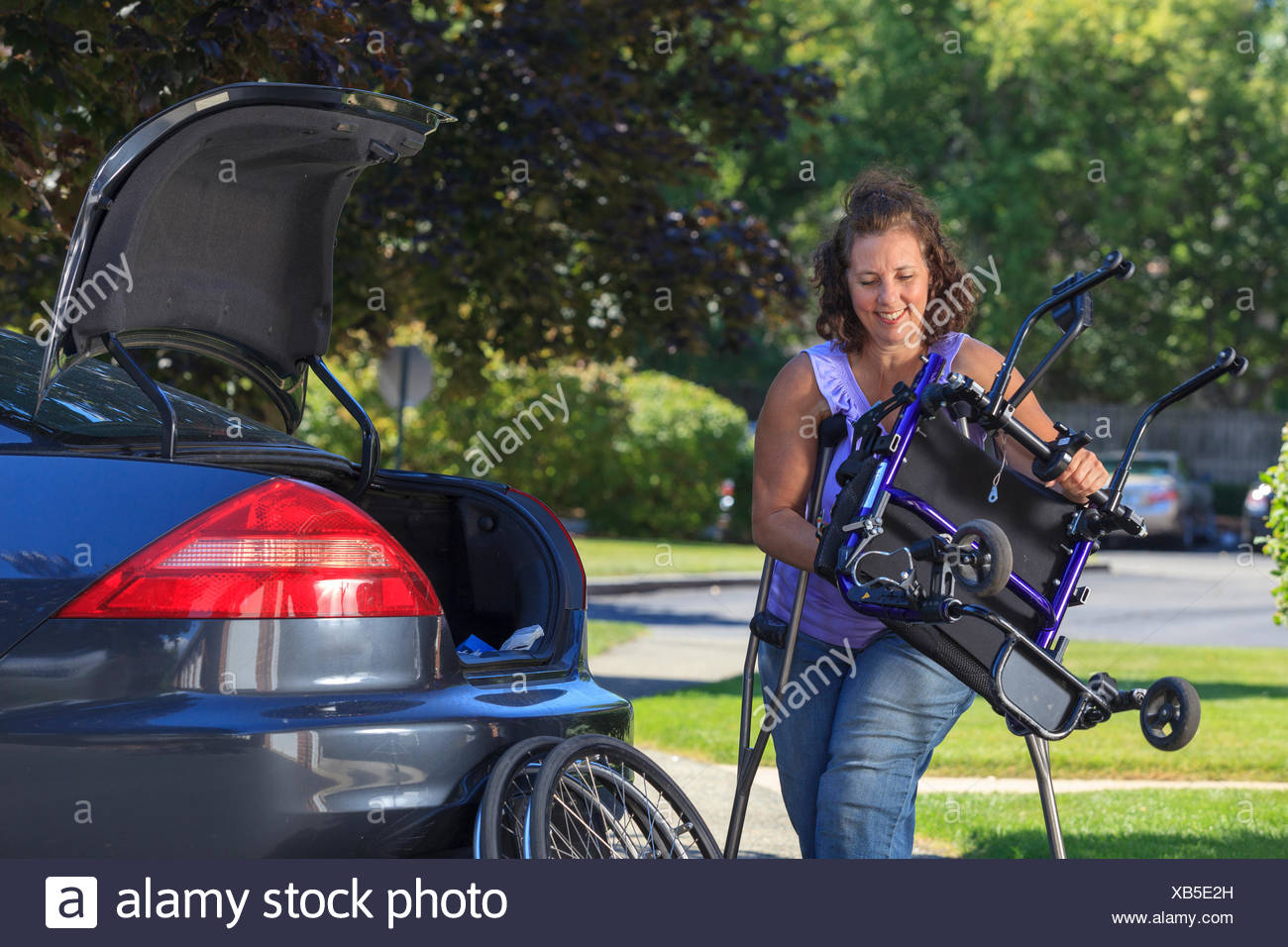 Woman with Spina Bifida taking apart wheelchair to put it in the back of car - Stock Image