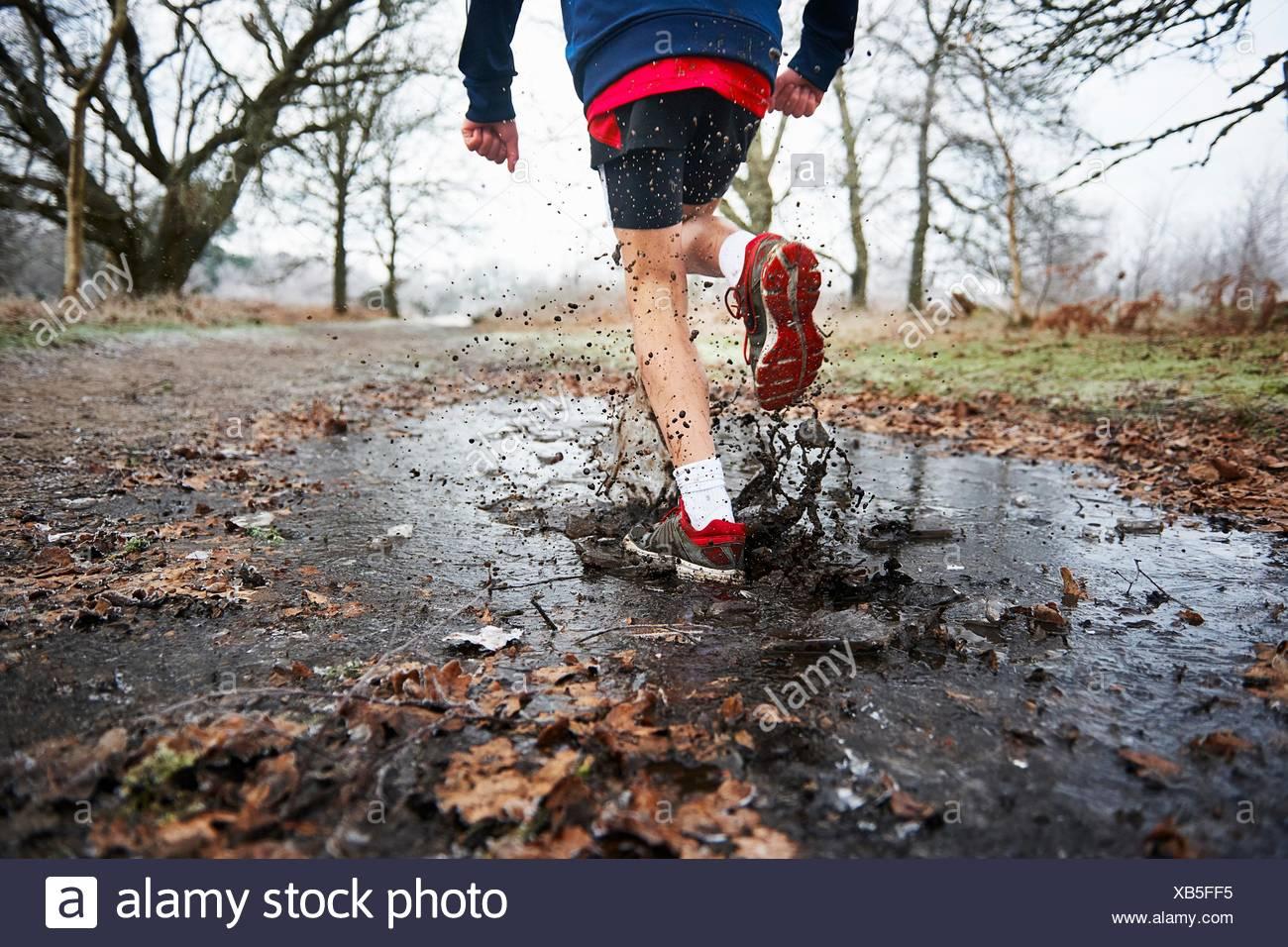 Rear view of teenage boy running through puddle splashing - Stock Image