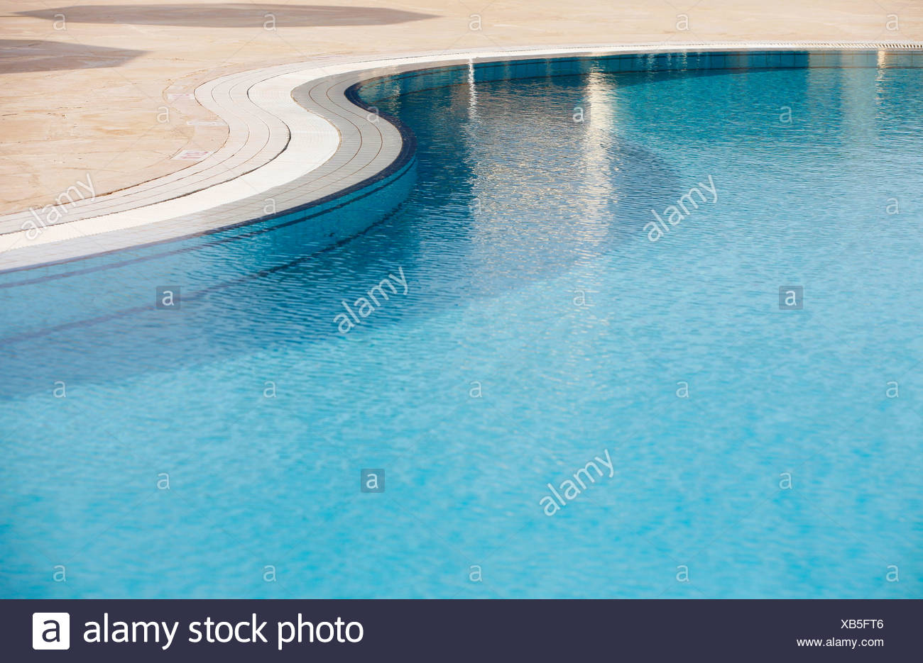 Rippled water surface in a swimming pool, detail, blue with steps below the surface - Stock Image
