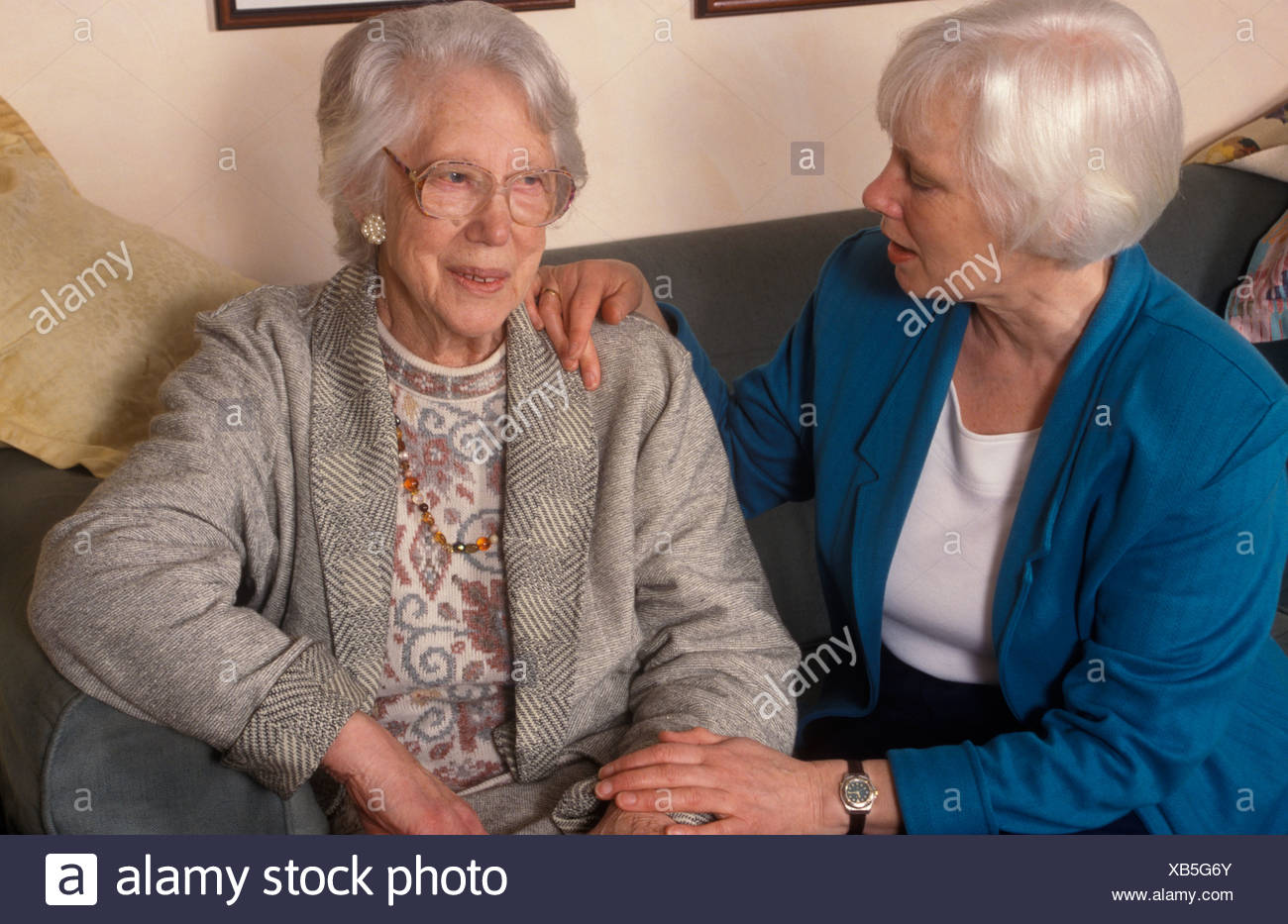 elderly woman being comforted by a daughter or relative - Stock Image