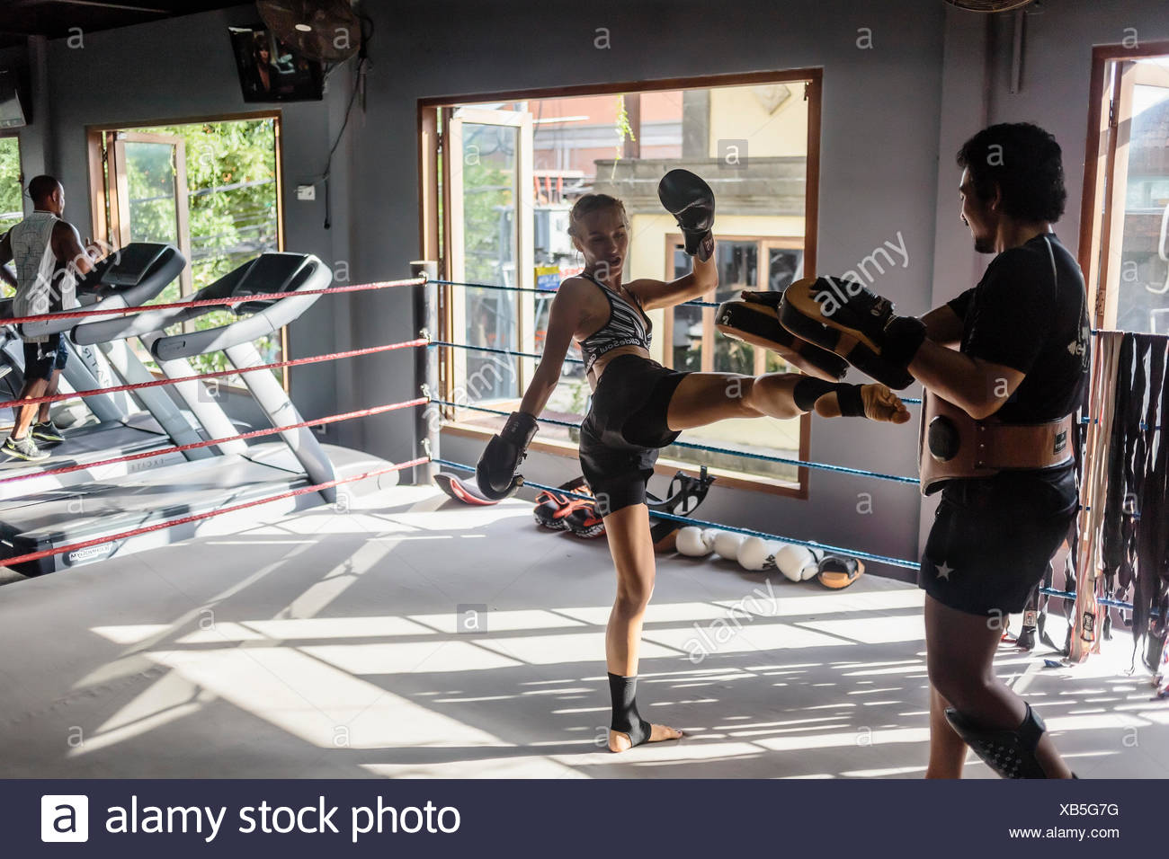Photograph of young woman kicking while practicing kickboxing with coach, Seminyak, Bali, Indonesia - Stock Image