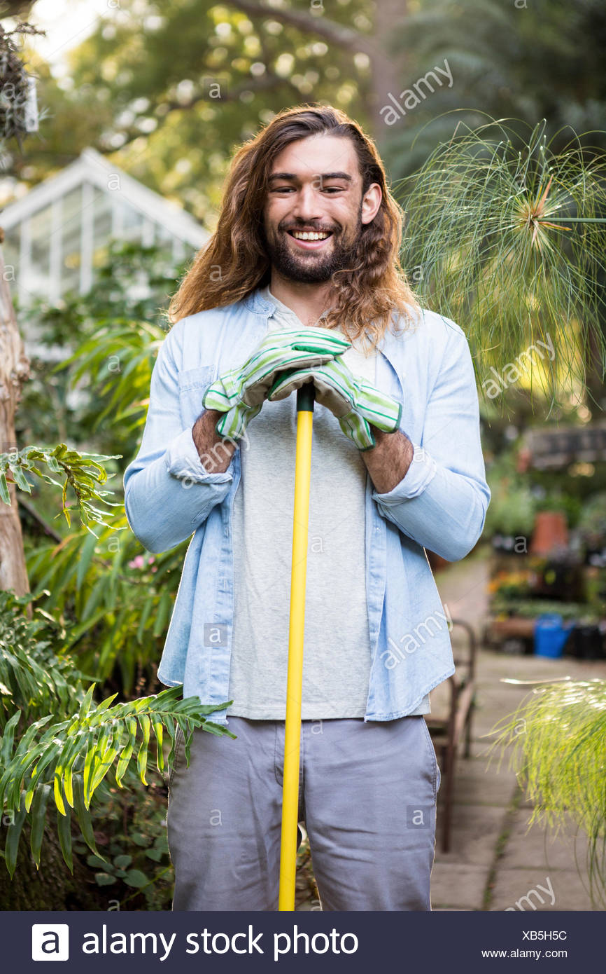 Portrait of happy gardener with long hair holding tool at garden - Stock Image
