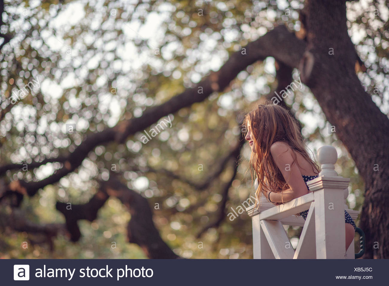 Girl leaning against wooden fence in backyard Stock Photo