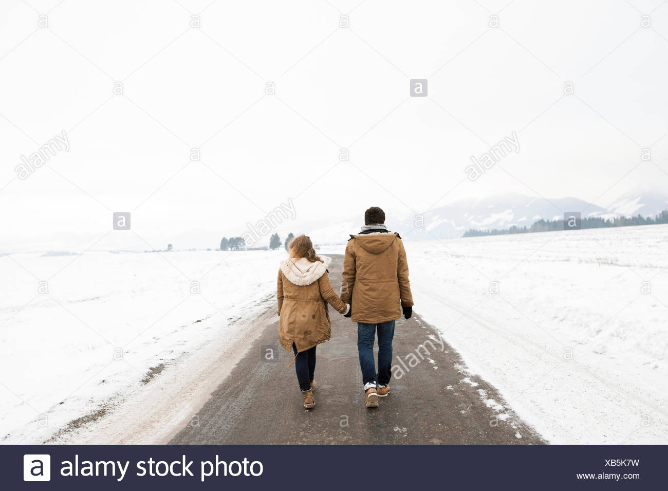Back view of young couple in love walking hand in hand on country road in snow-covered landscape - Stock Image
