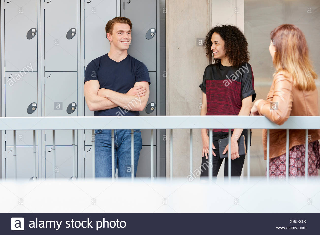 Three designers chatting on design studio balcony - Stock Image