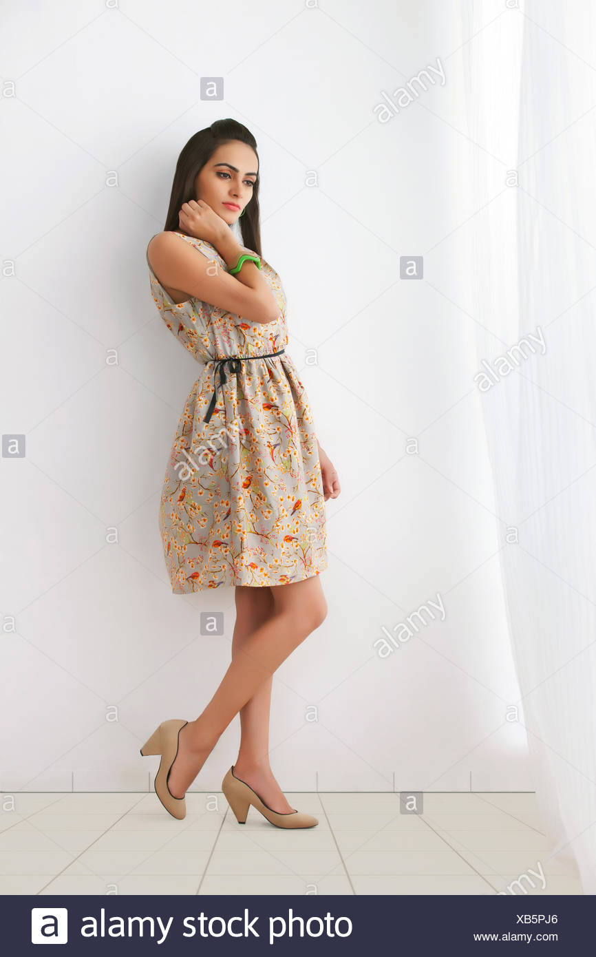 Full length of thoughtful young woman in sundress against white wall - Stock Image