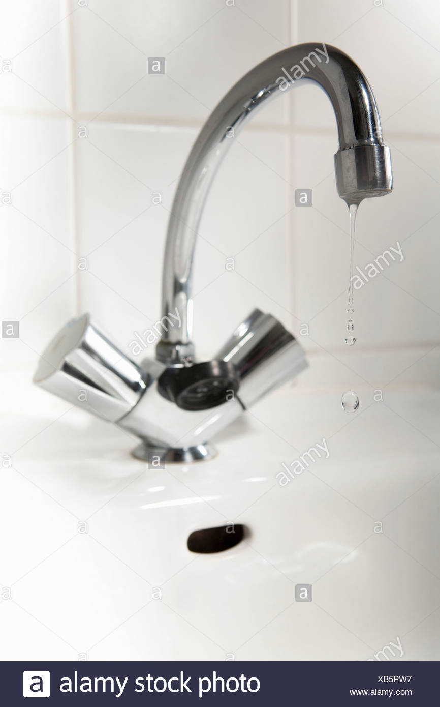 Water dripping from a bathroom faucet - Stock Image
