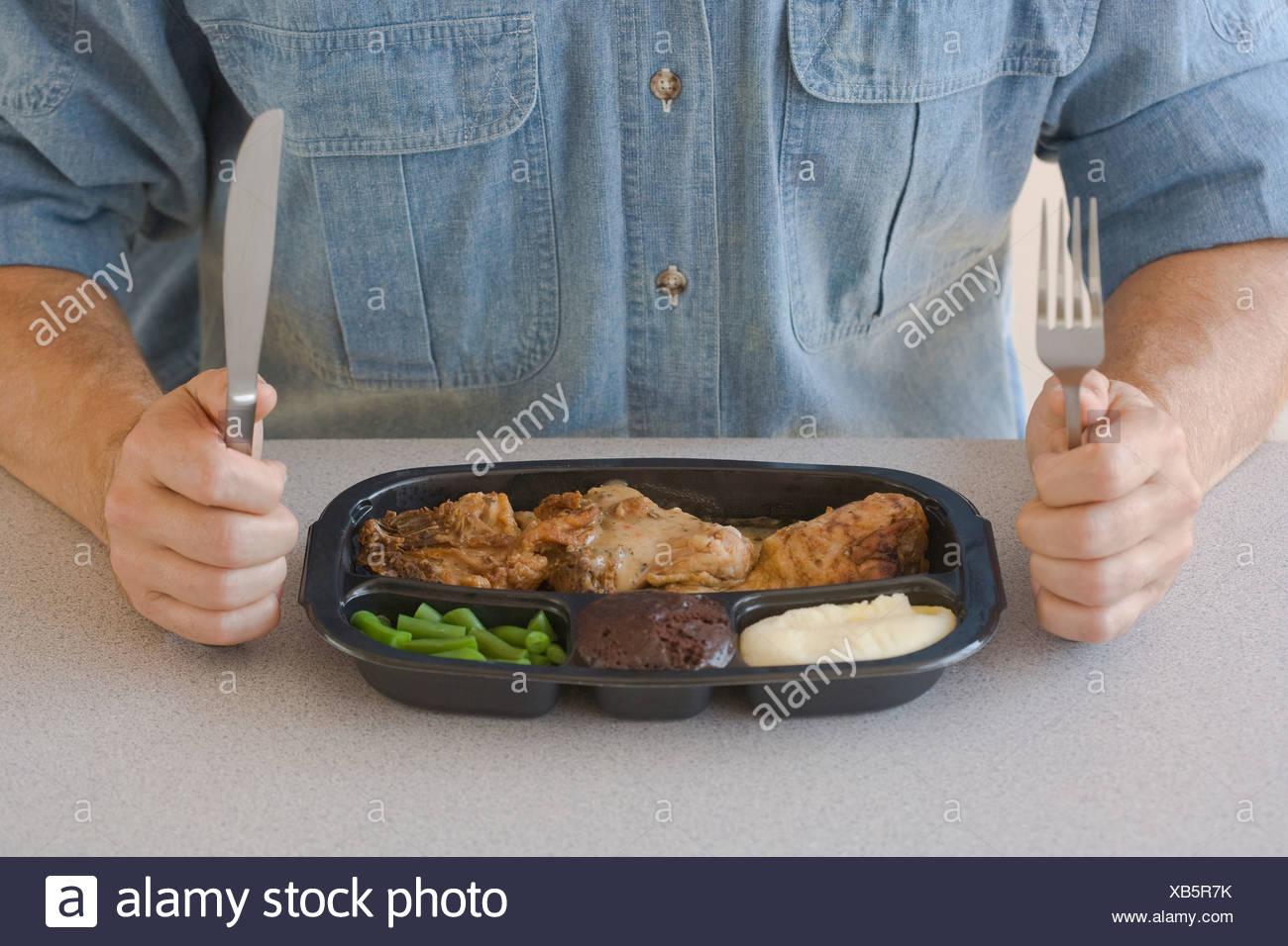 Man eating TV dinner - Stock Image