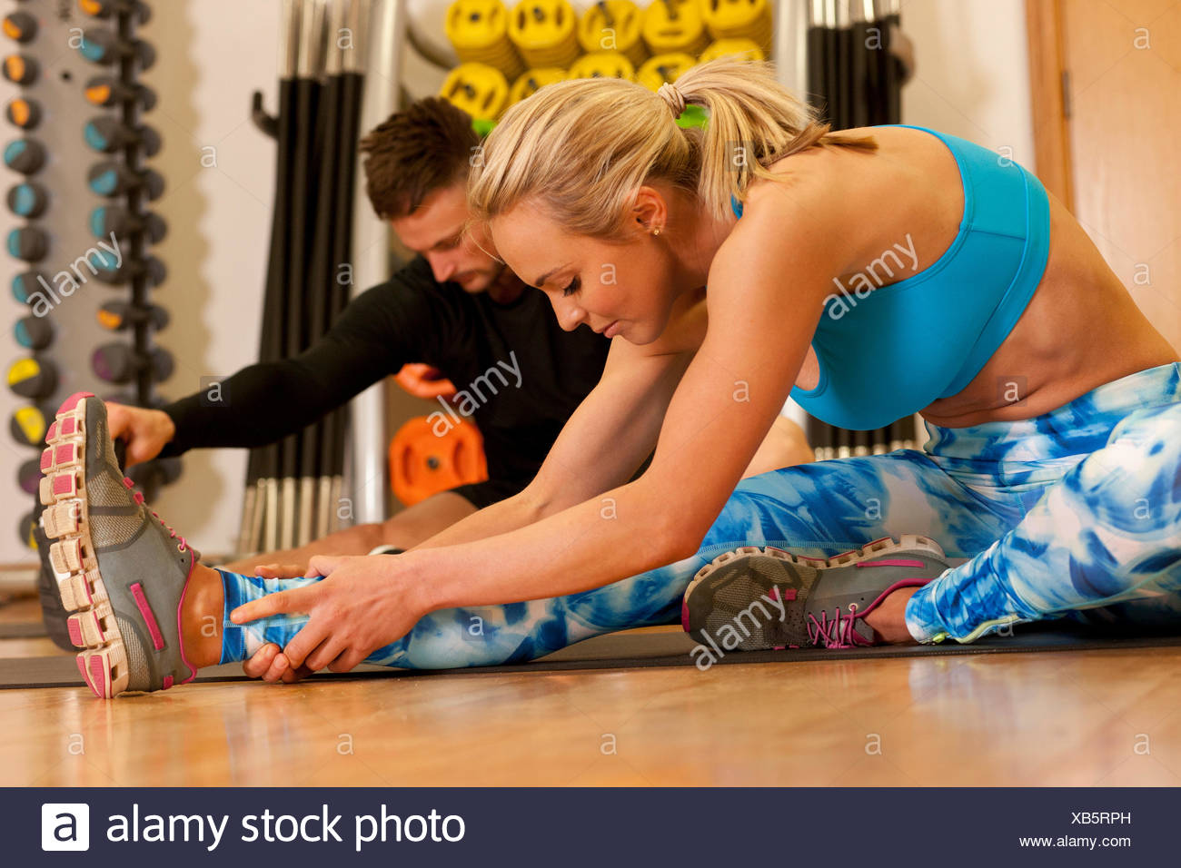 Man and woman in gym sitting on floor doing leg stretching exercises Stock Photo