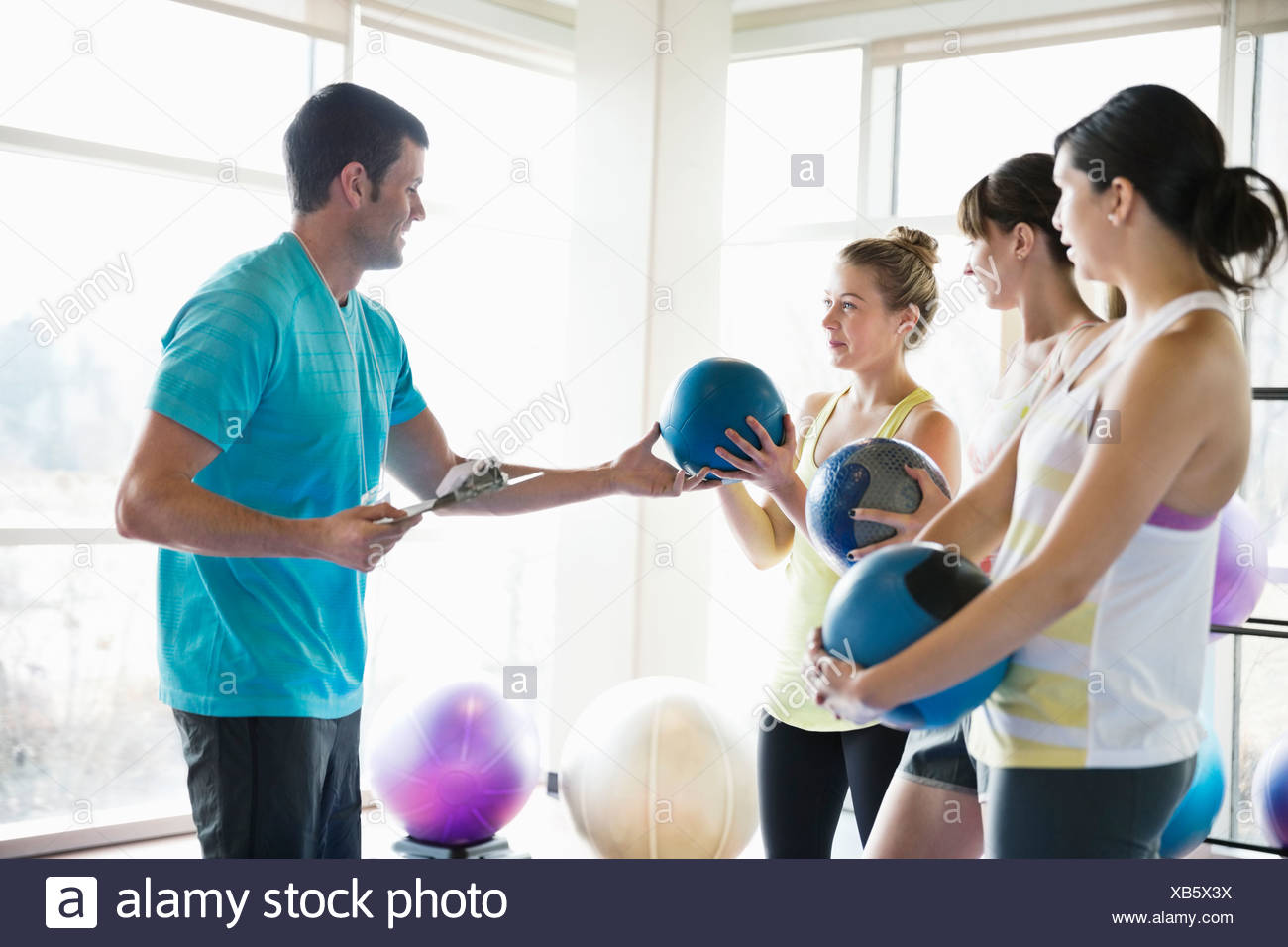 Instructor handing medicine ball to woman in fitness class - Stock Image