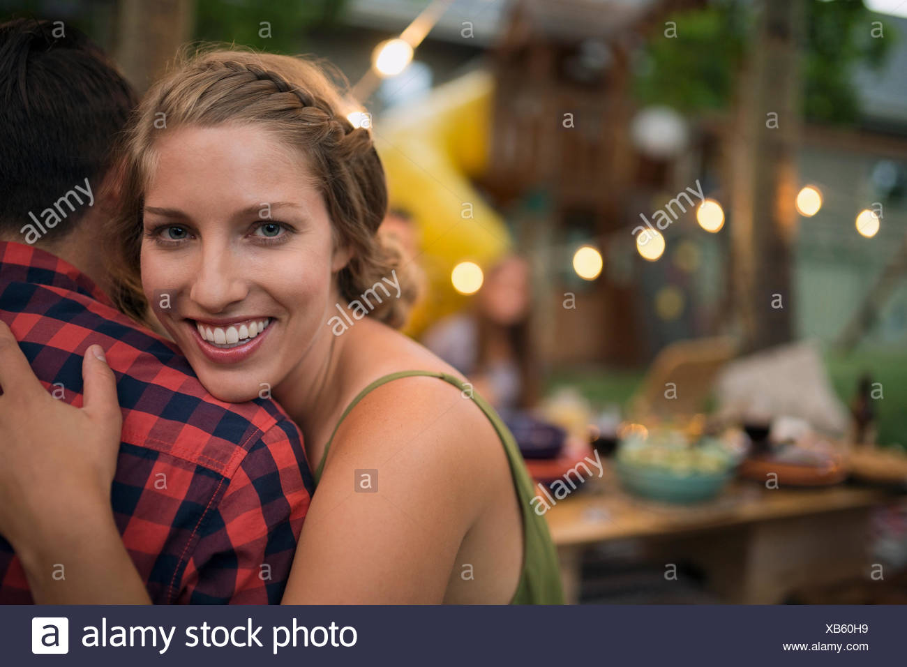 Portrait smiling girlfriend hugging boyfriend - Stock Image