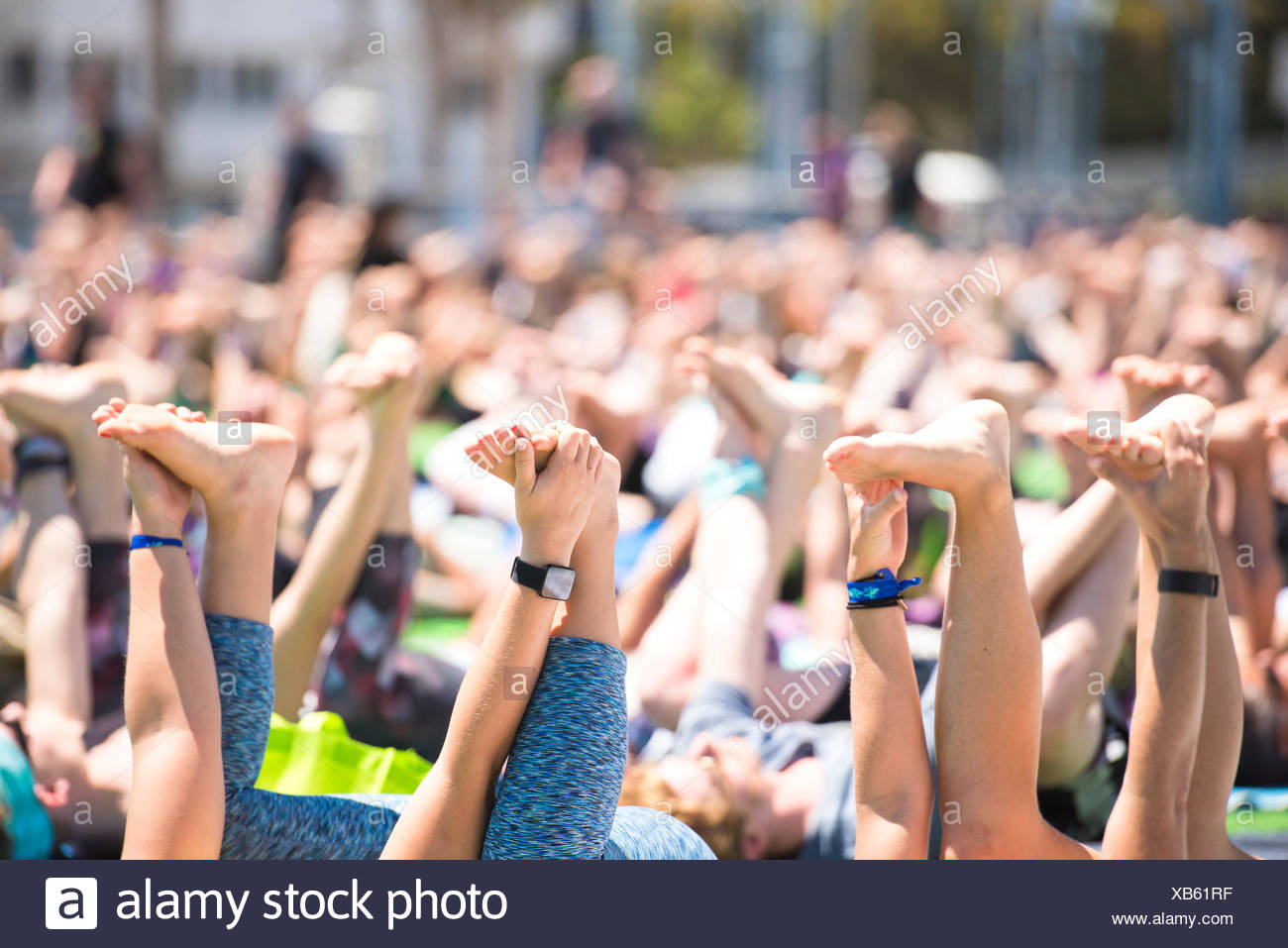 Close up of people hands and feet doing happy baby pose during outdoor yoga festival in Santa Monica, California, USA - Stock Image