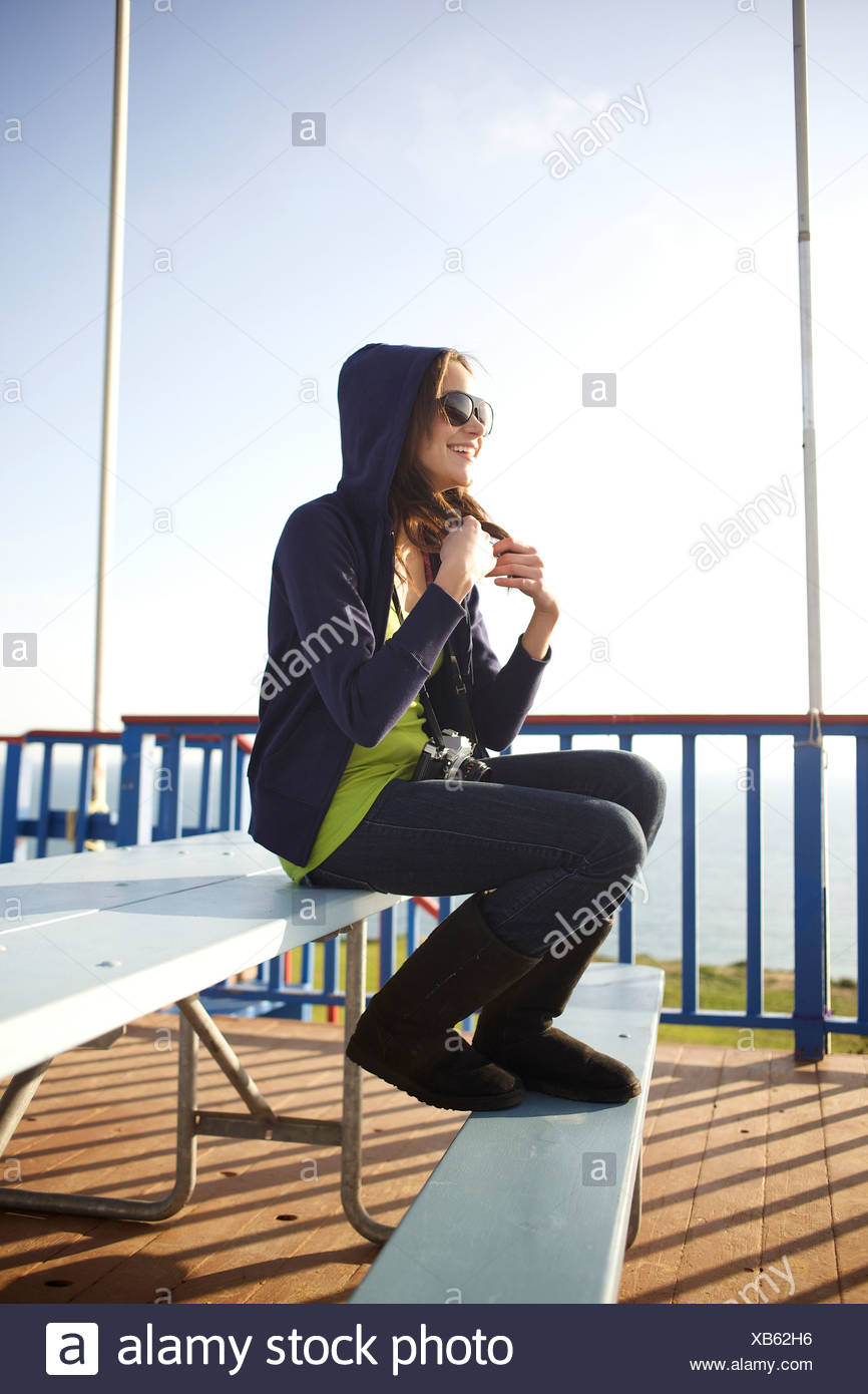 Female in her early 20's watches paragliders at the paragliding port in Torrey Pines, San Diego, California. - Stock Image