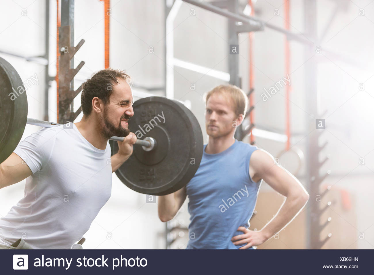 Man assisting friend in lifting barbell at crossfit gym - Stock Image