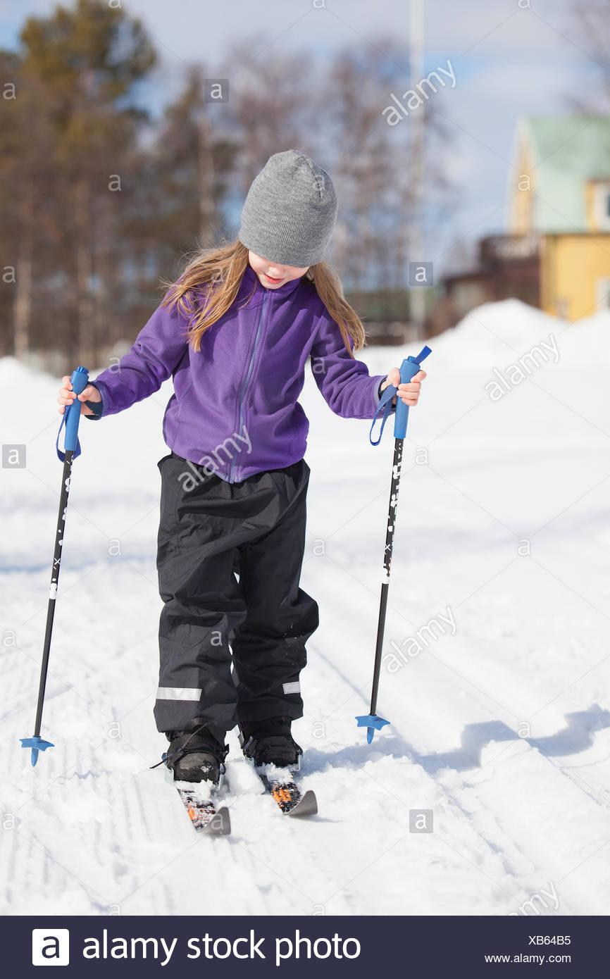 Sweden, Norrbotten, Gallivare, Girl (4-5) skiing in winter - Stock Image