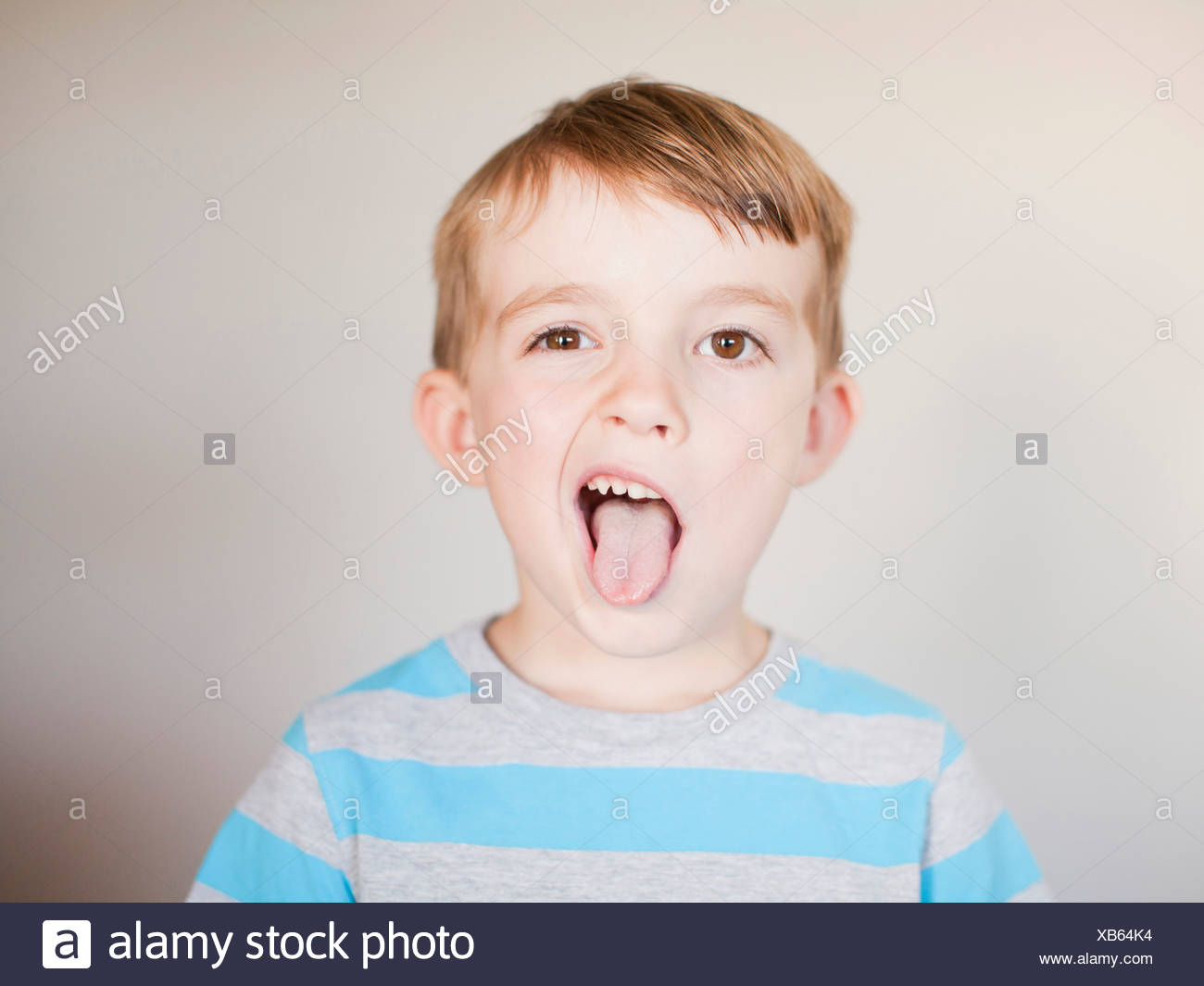 Studio Shot, Portrait of boy sticking out his tounge - Stock Image