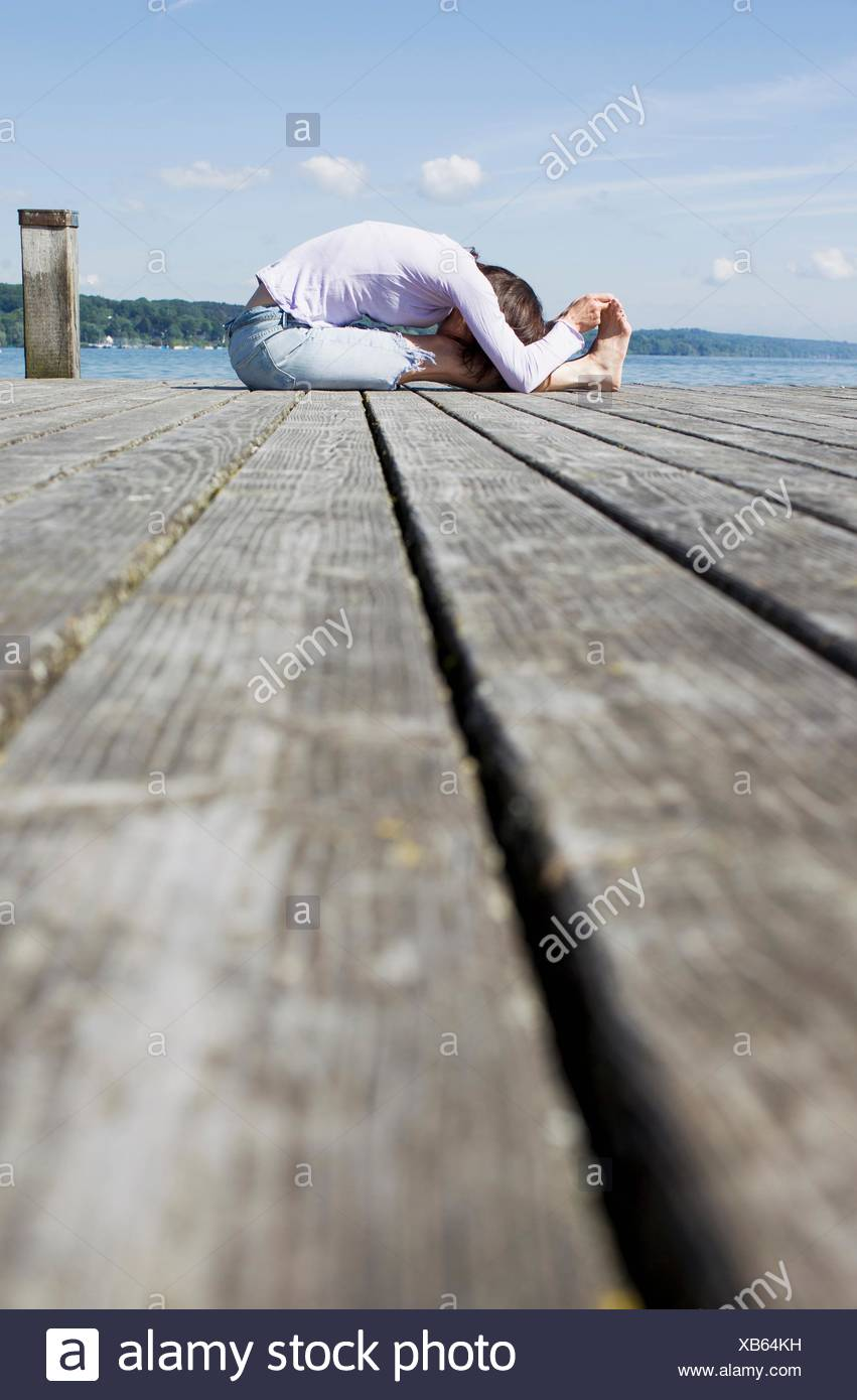 Surface level side view of mature woman sitting on pier bending over touching toes - Stock Image