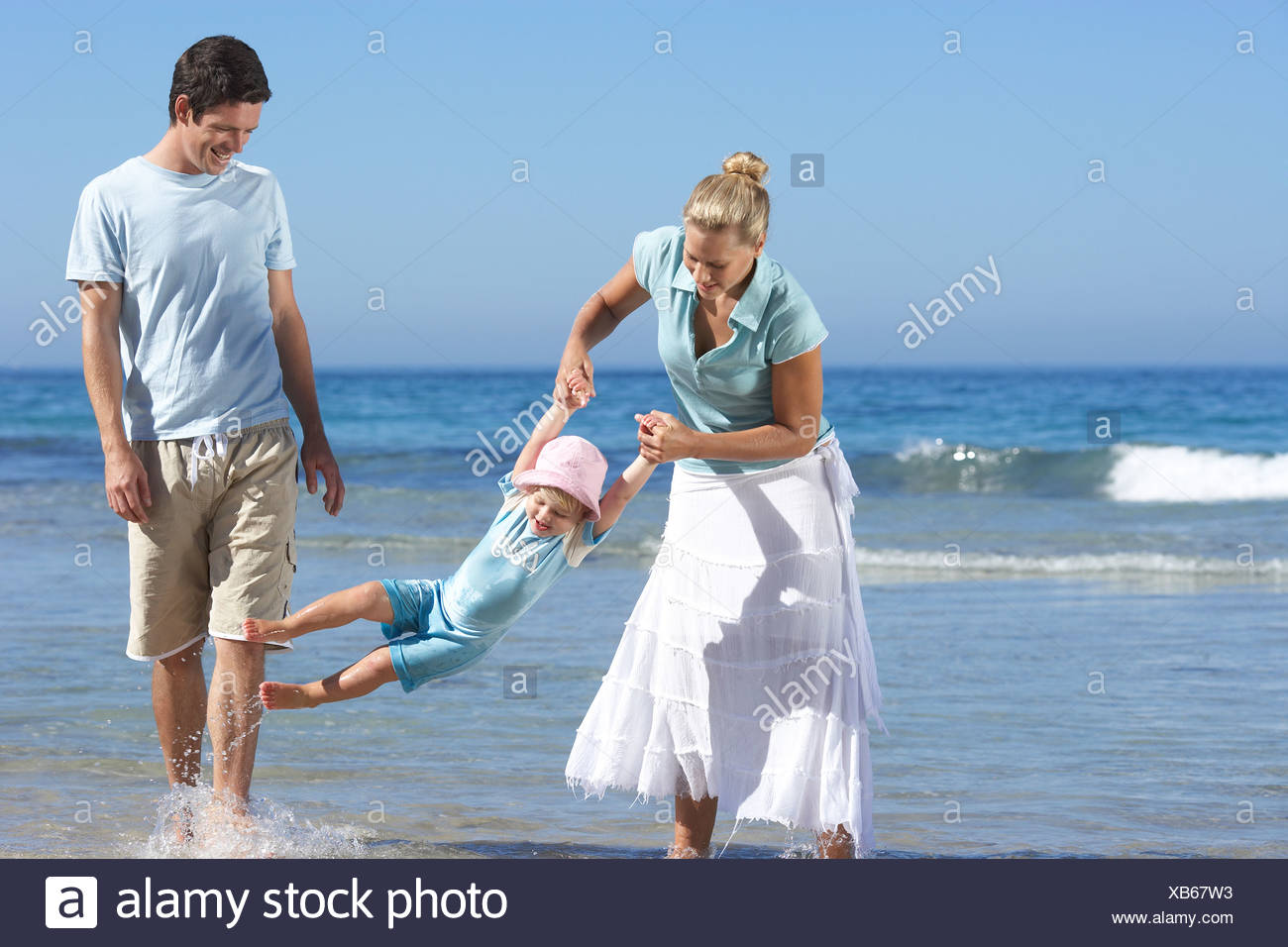Family walking along beach ankle deep in water mother swinging daughter 2 4 smiling - Stock Image