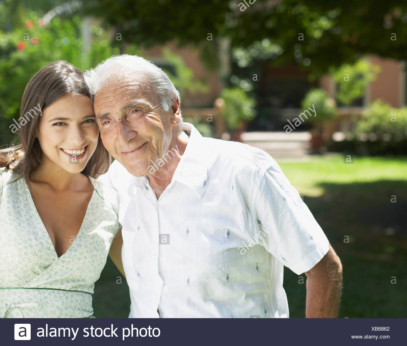 Senior man standing outdoors with arm around woman smiling - Stock Image