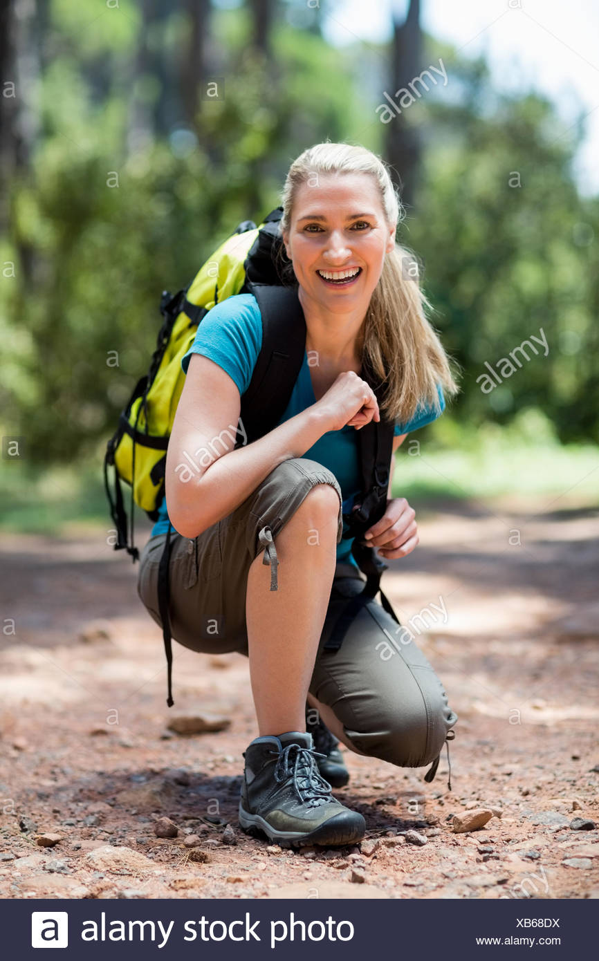 Woman smiling and squatting - Stock Image