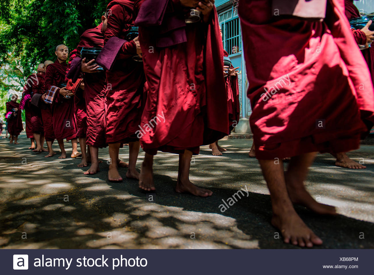 Mahagandayon Monastery, Amarapura, Myanmar, South East Asia. Monks in a row for the ritual of lunch. - Stock Image