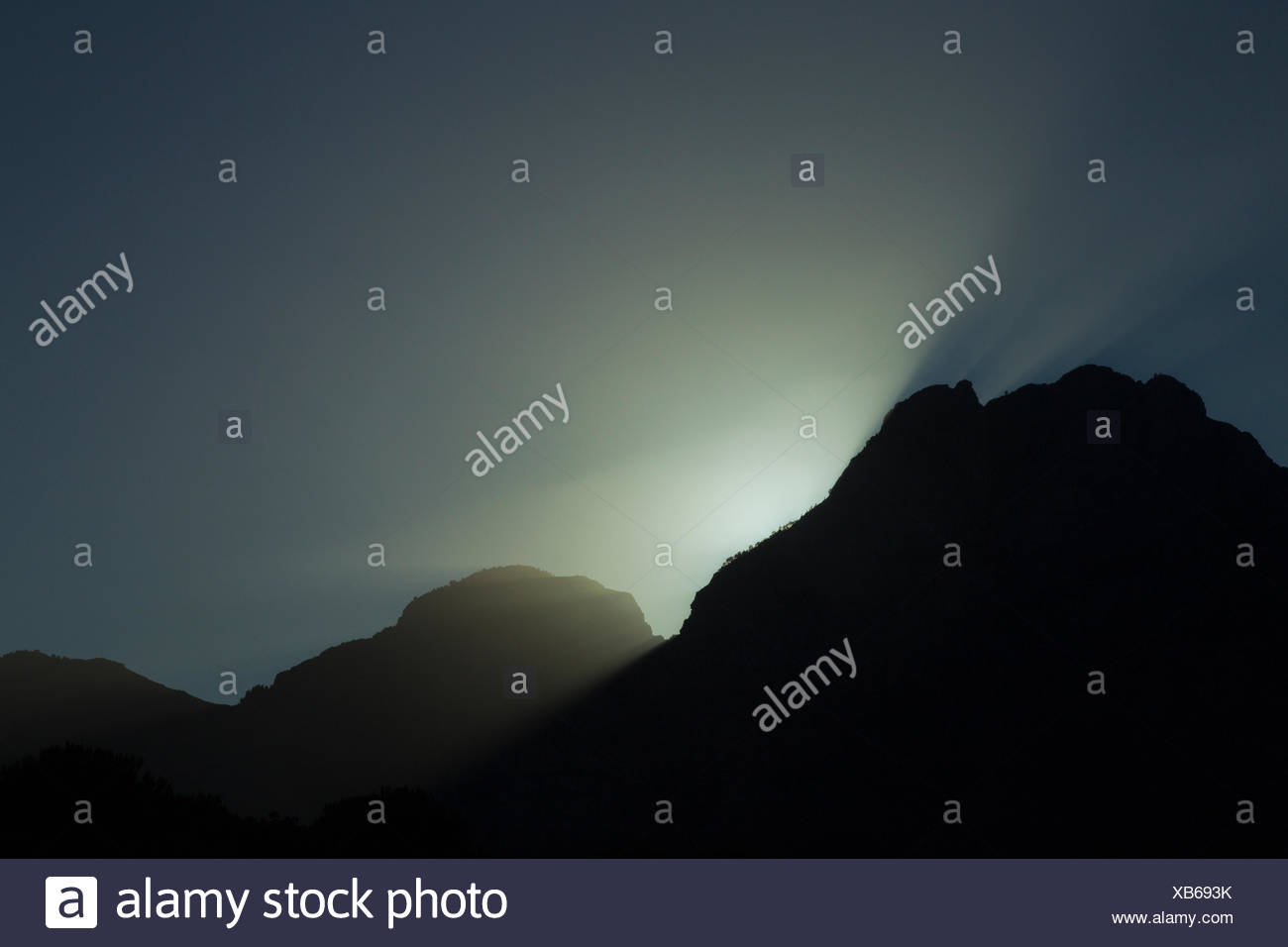 Light shines over the mountains as the sun goes down. - Stock Image
