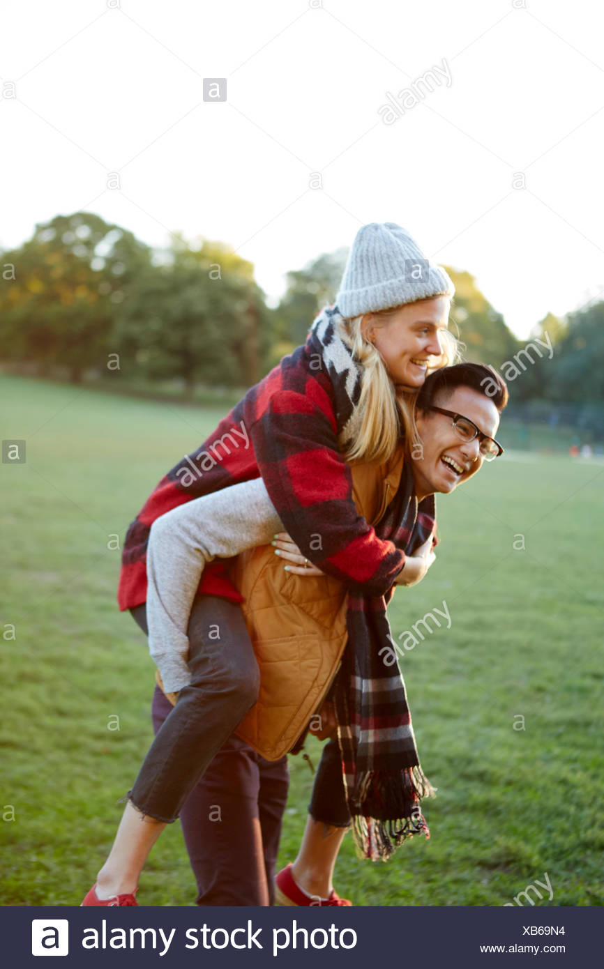 Man giving girlfriend a piggyback in park - Stock Image