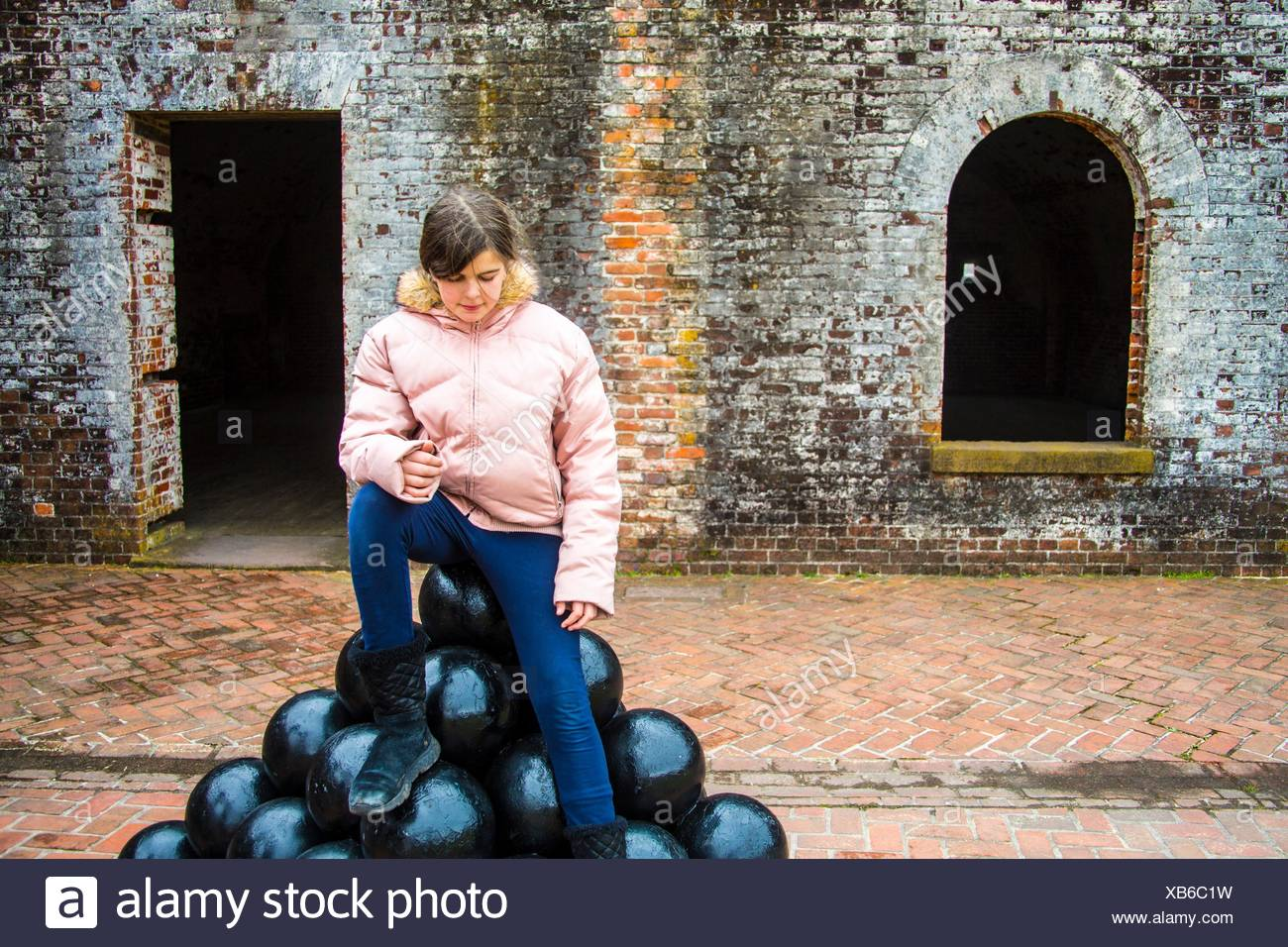 beautiful preteen caucasian girl sitting on a pyramid pile of canon balls in an old fort. She is dress warmly and look thoughtful. - Stock Image