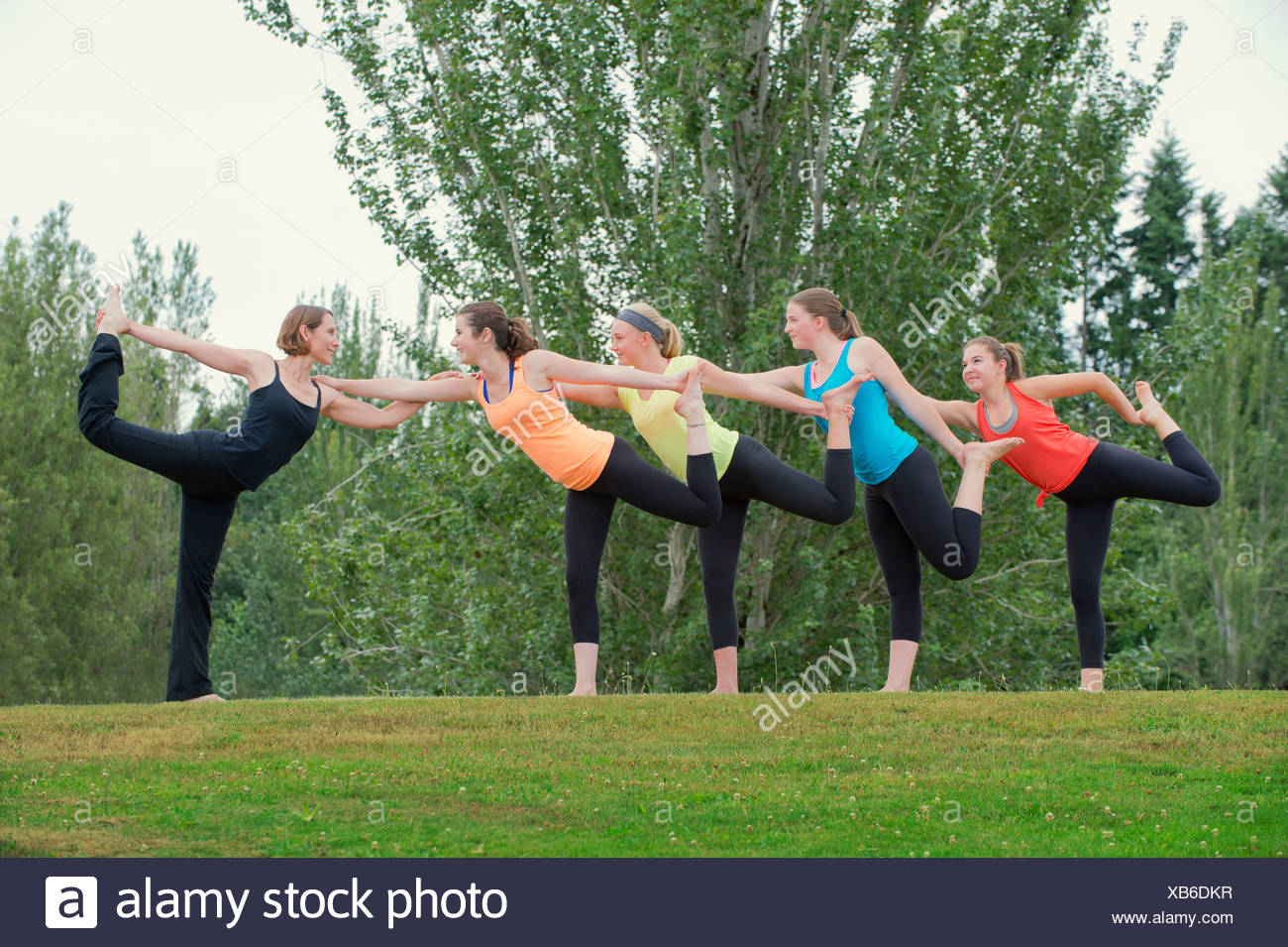 Teenage girls and yoga tutor standing on one leg - Stock Image