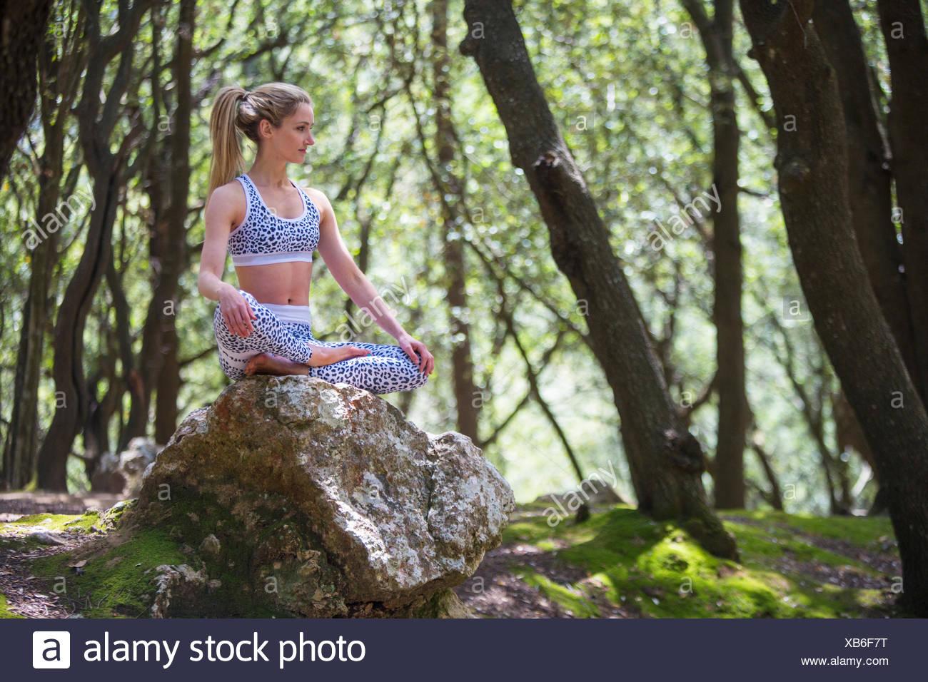 Woman on rock sitting cross legged meditating - Stock Image