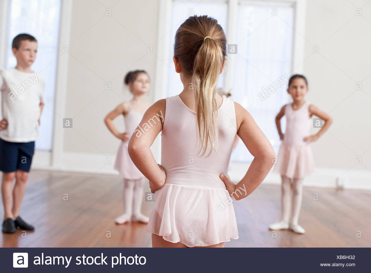 Four children practicing ballet with hands on hips in ballet school - Stock Image