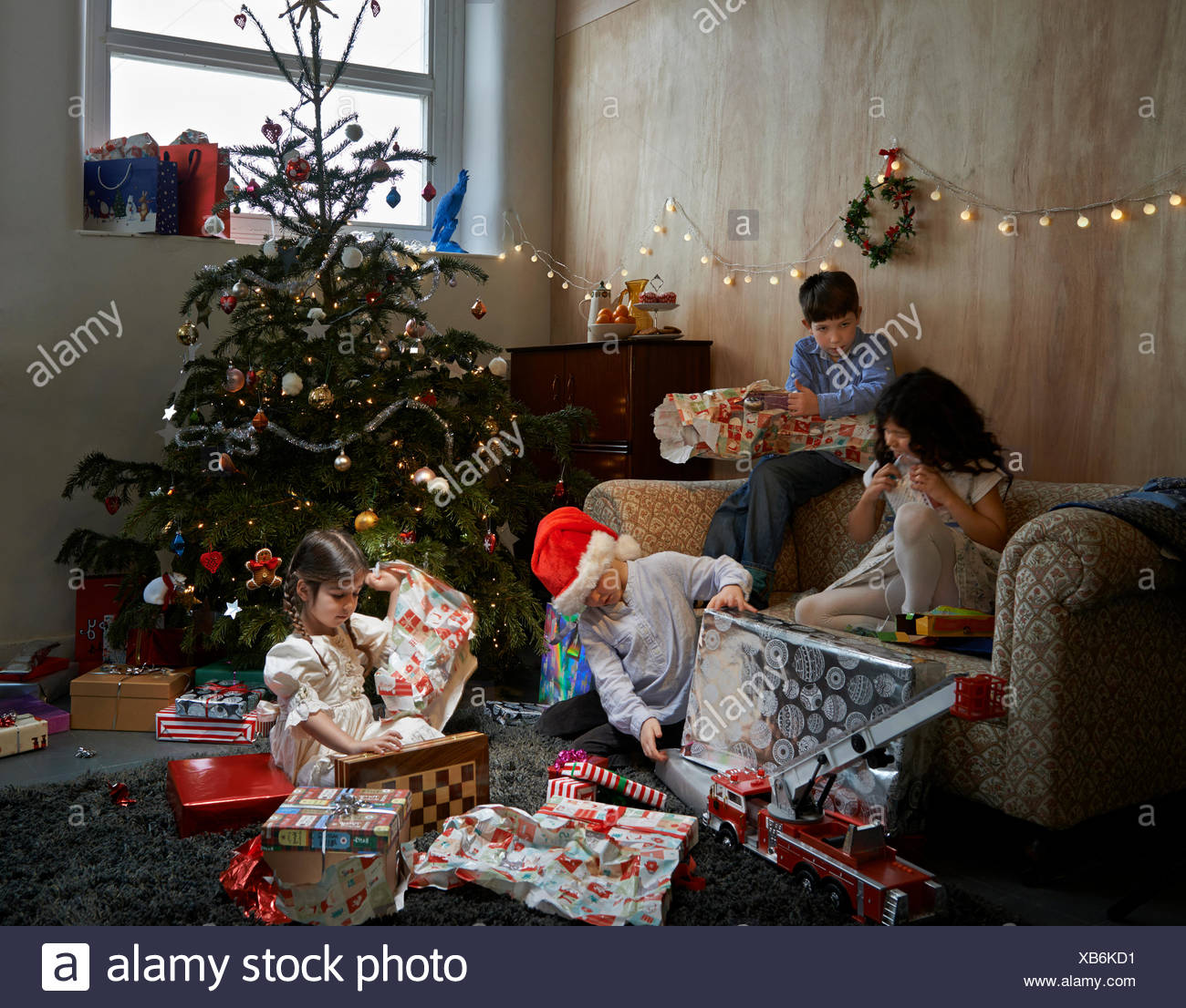 Sisters and brothers opening christmas gifts in sitting room Stock Photo