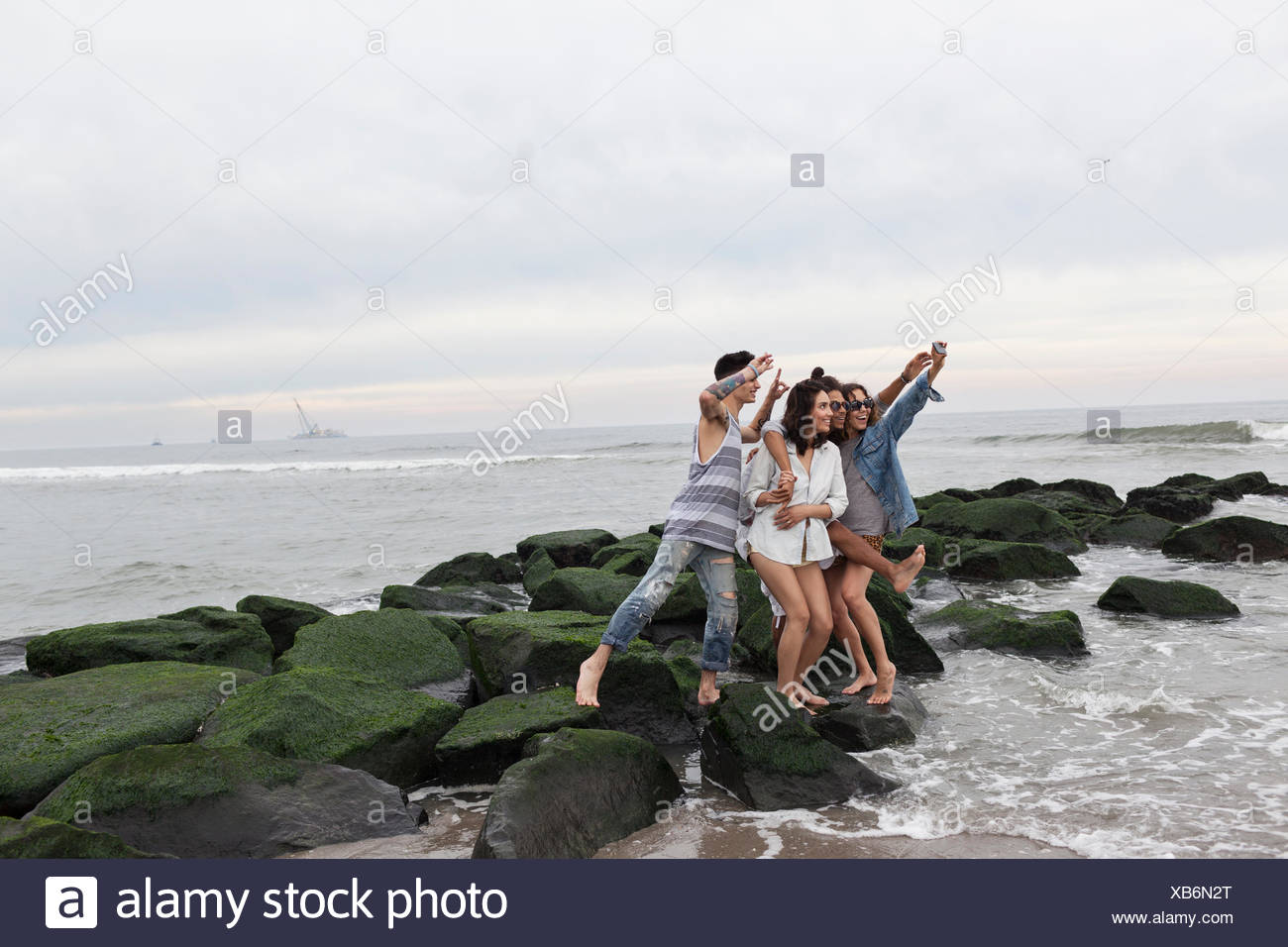 Friends posing for a selfie on the beach - Stock Image