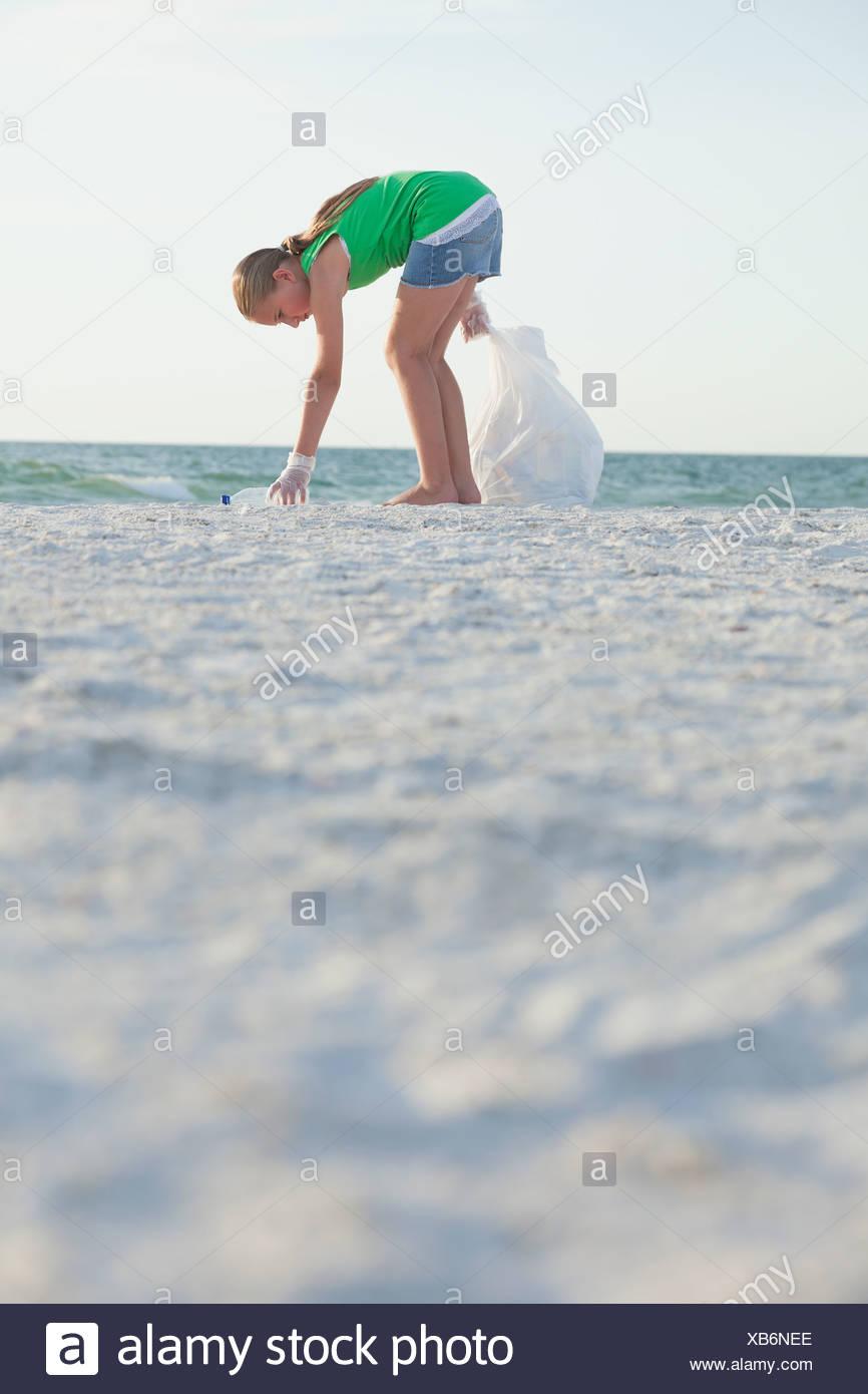 USA, Florida, St. Petersburg, Girl (10-11) cleaning beach - Stock Image