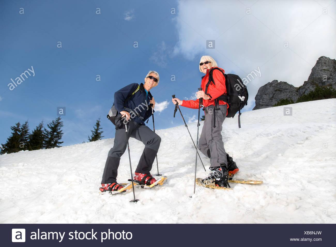 senior couple snowshoeing in mountains Stock Photo