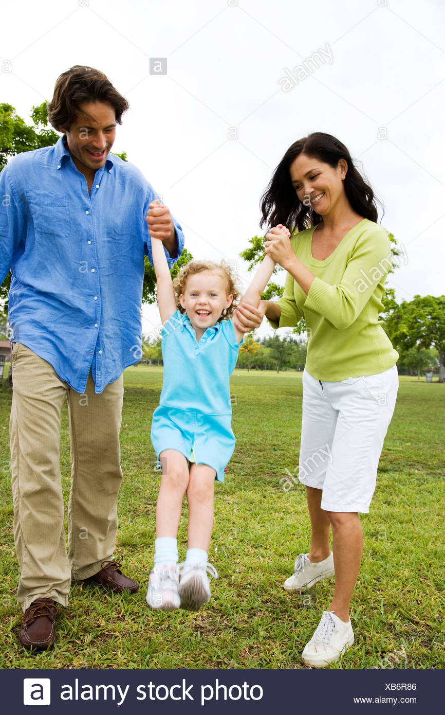 Parents playing with their daughter in the park - Stock Image