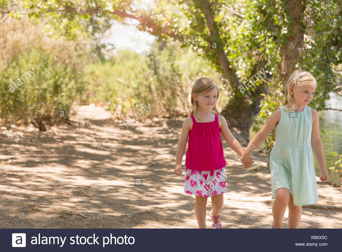 Two young sisters strolling and holding hands on riverbank - Stock Image