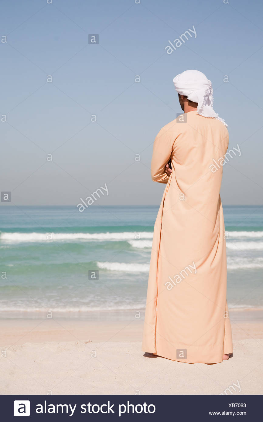 Middle Eastern man standing on the beach - Stock Image