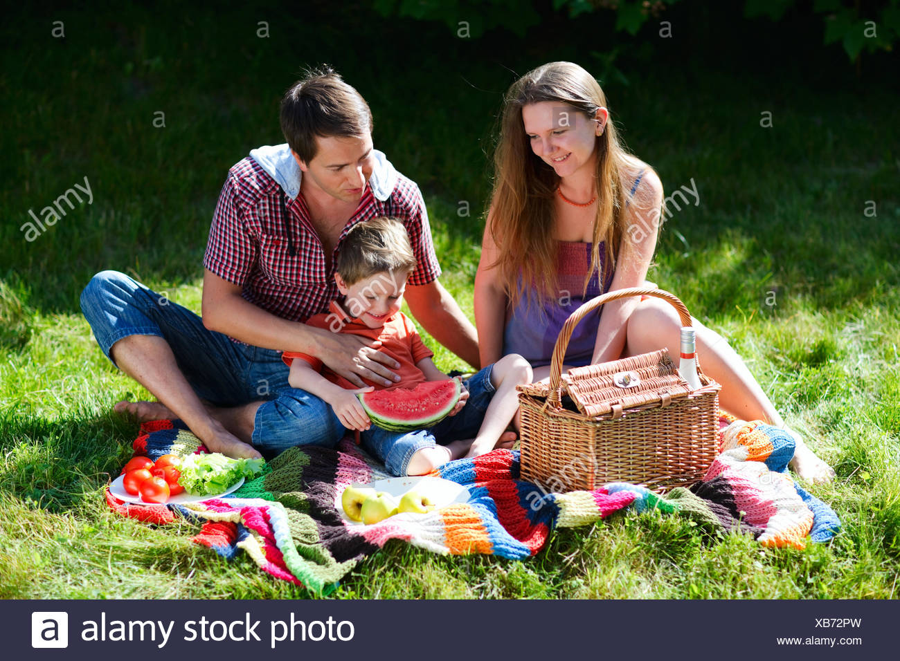 Young family having picnic on summer sunny day - Stock Image