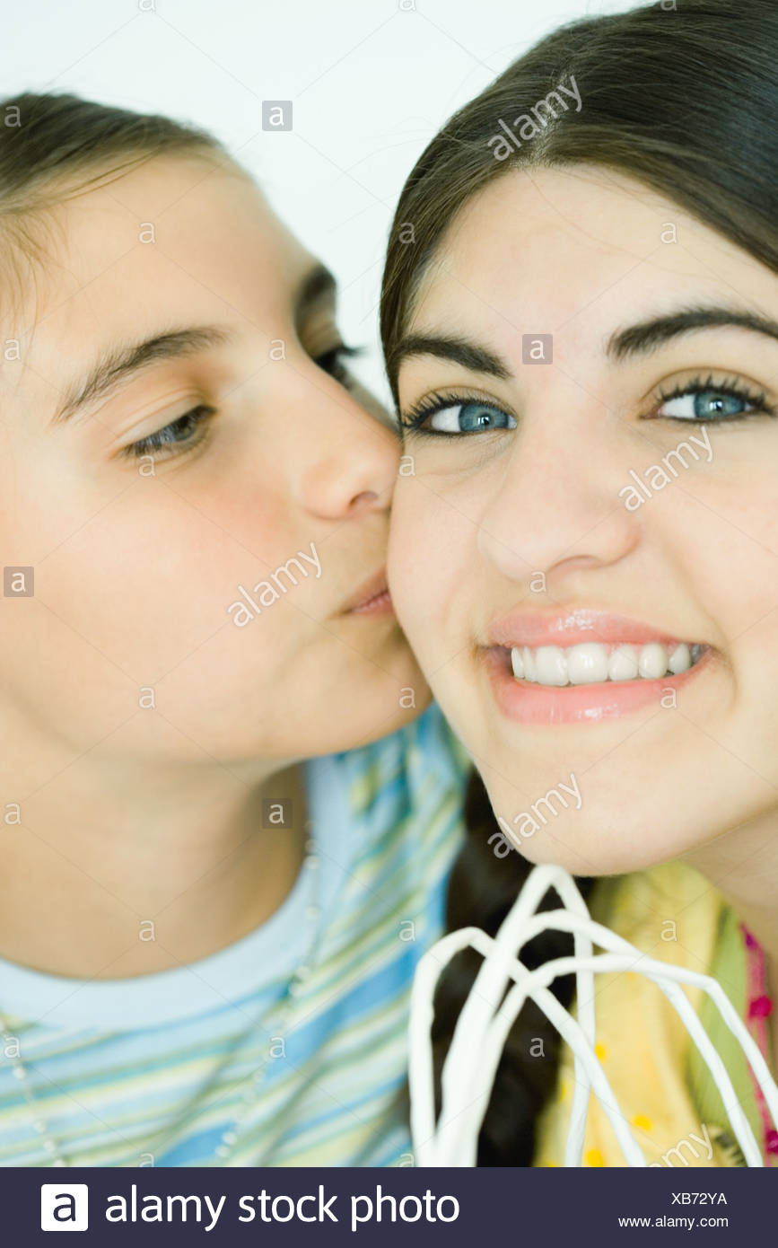 Two young female friends, one kissing the other on the cheek Stock Photo