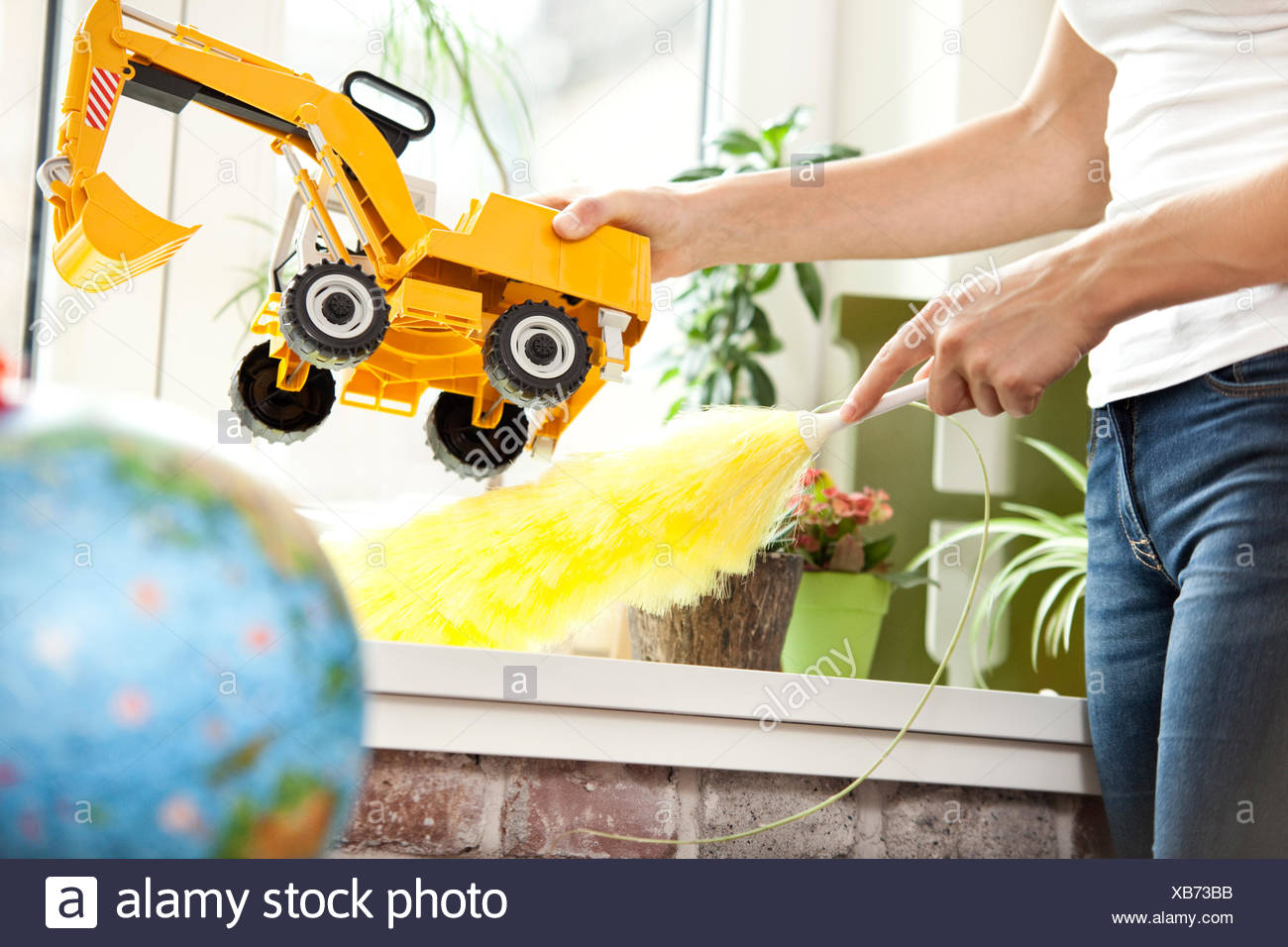 Woman cleansing windowsill in children's room Stock Photo
