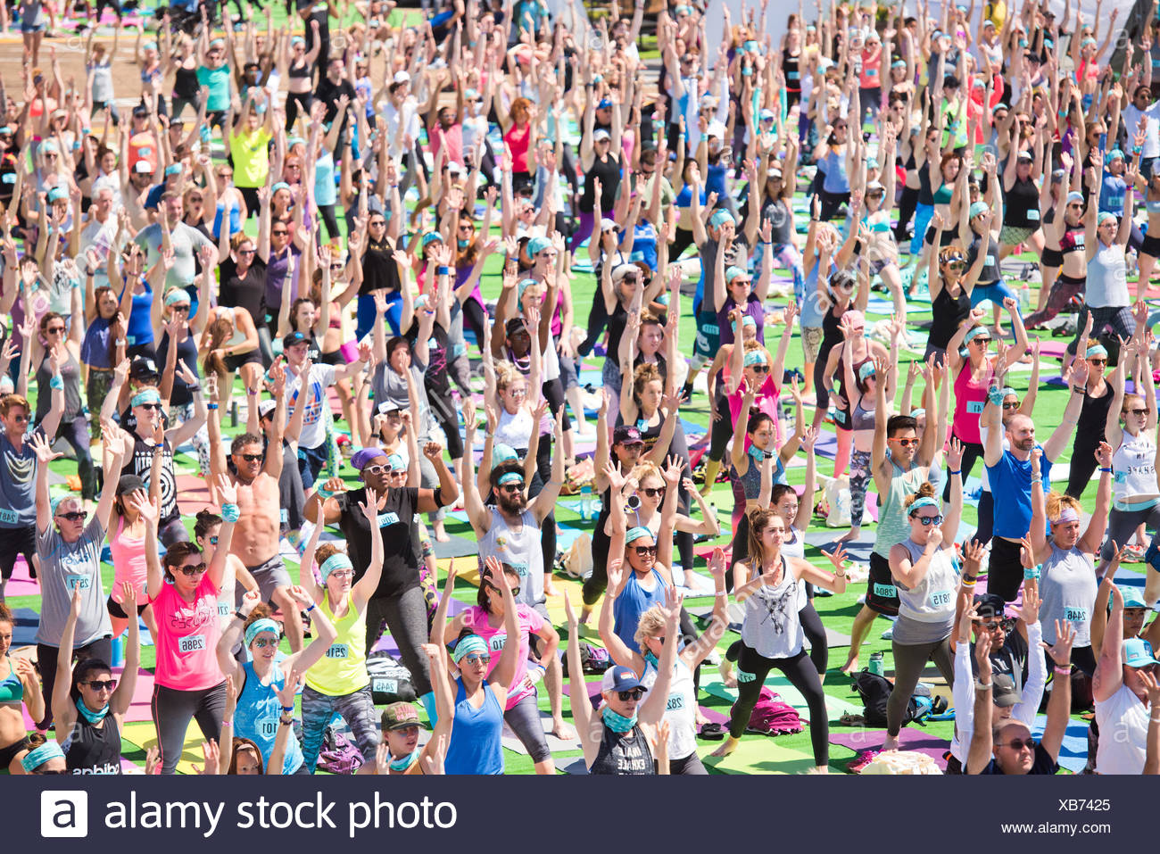 People performing warrior 1 during outdoor yoga festival on Santa Monica Pier in Santa Monica, California, USA - Stock Image