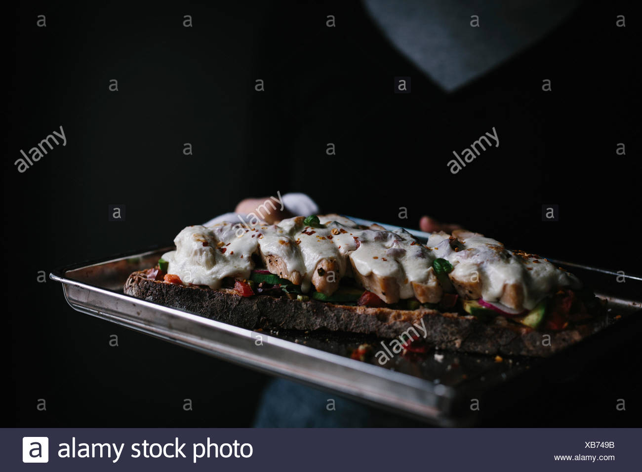 A woman is holding a chicken caprese open faced (tartine) sandwich that just came out of the oven. - Stock Image