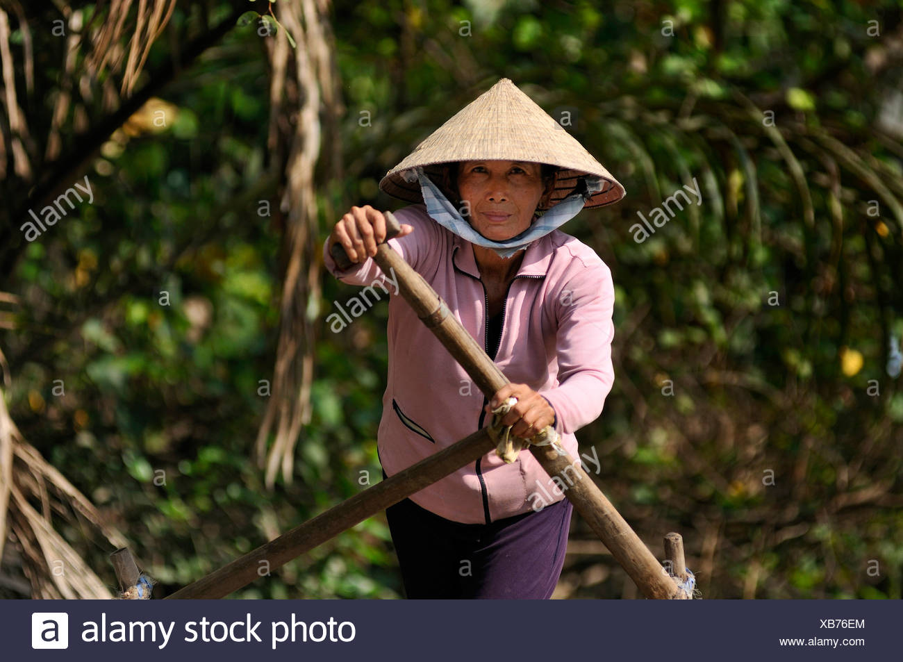 Woman with a traditional hat, cone-shaped hat made of palm leaves, rowing a wooden boat full of fruit on the mekong, Can Tho, M - Stock Image
