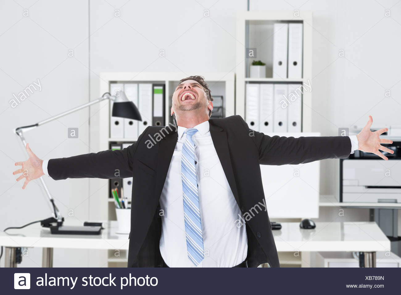 Businessman Laughing While Standing With Arms Outstretched - Stock Image
