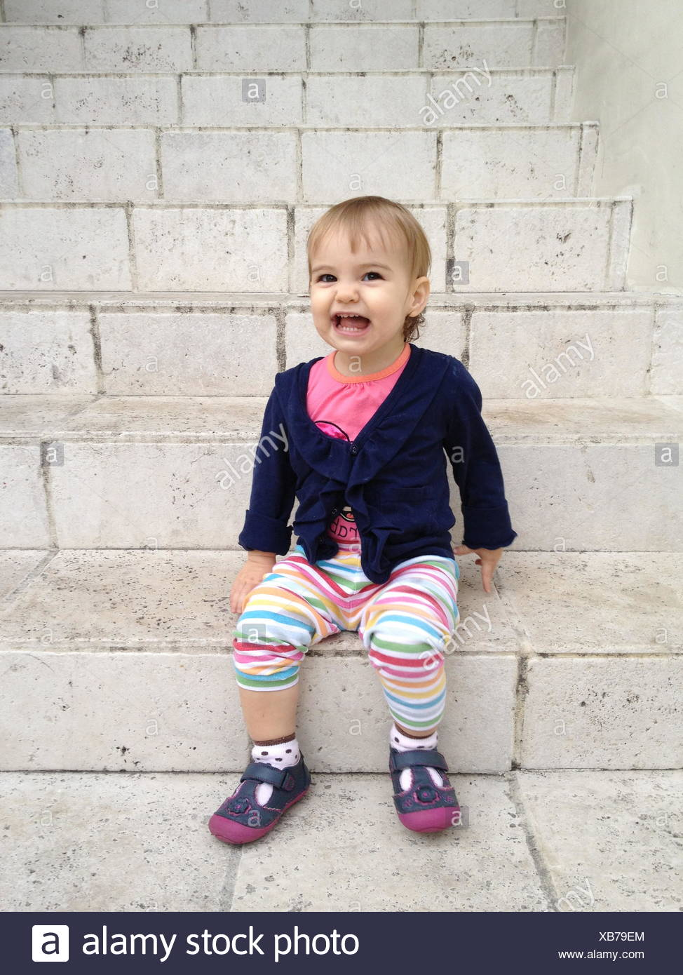 Portrait of girl (18-23 months) sitting on steps - Stock Image